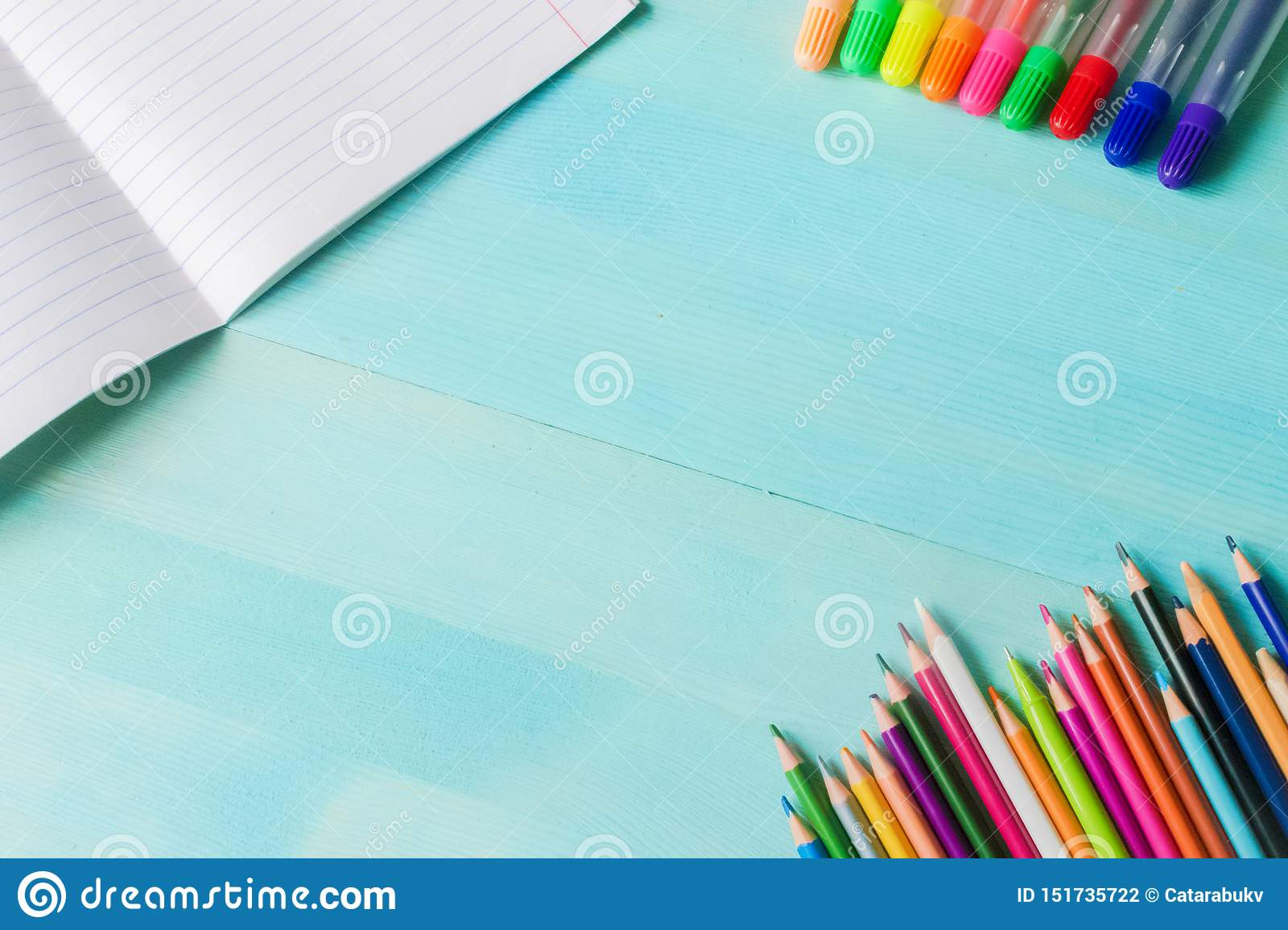 Concept back to school.School accessories, colored pencils, pen with empty notebook on blue wooden background