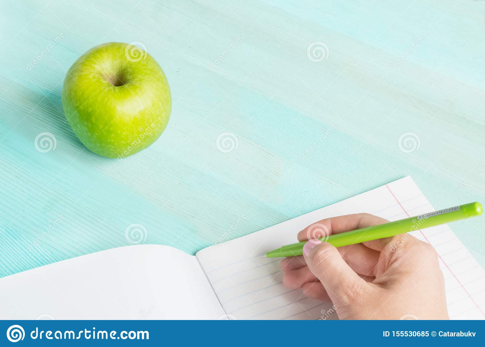 Concept back to school.School accessories, pen with empty notebook on blue wooden background