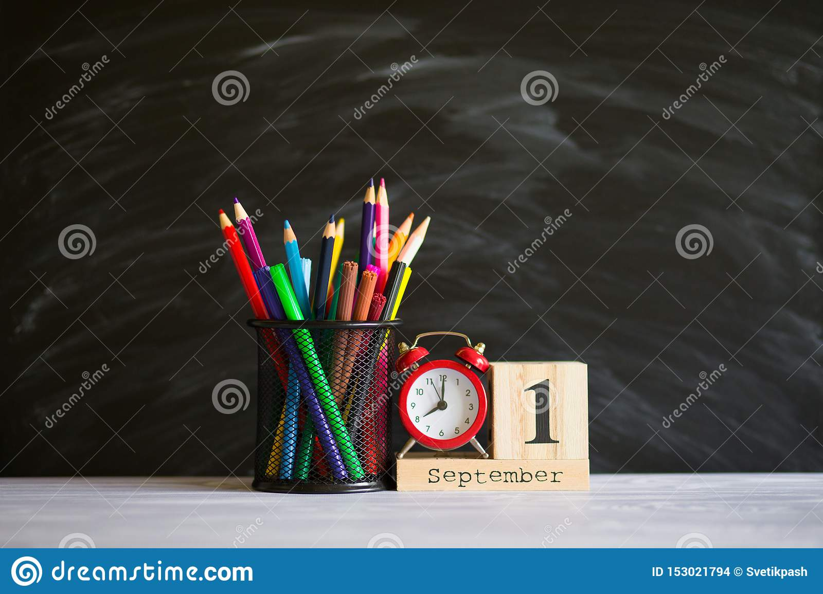 Concept back to school. Re alarm clock with color pencils and wooden calendar set on 1st september on blackboard background.
