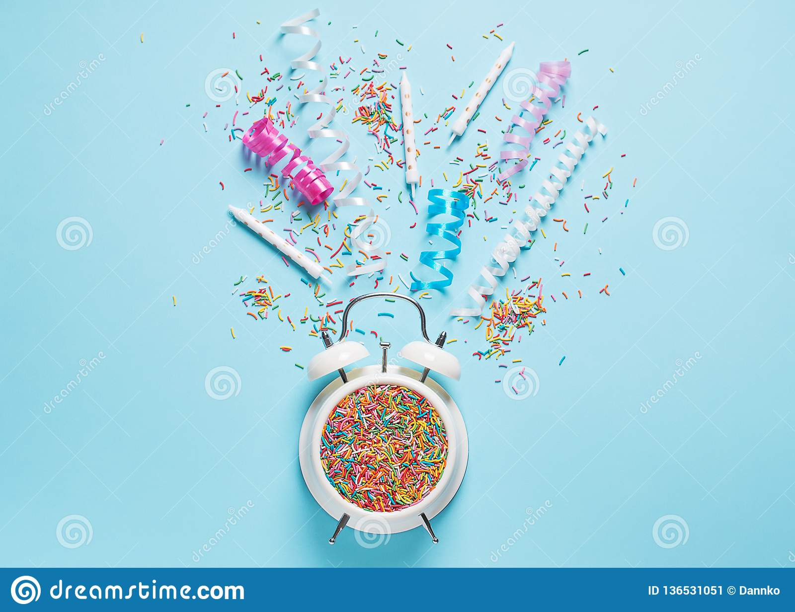 Concept of birthday and party time on blue pastel bakground with alarm