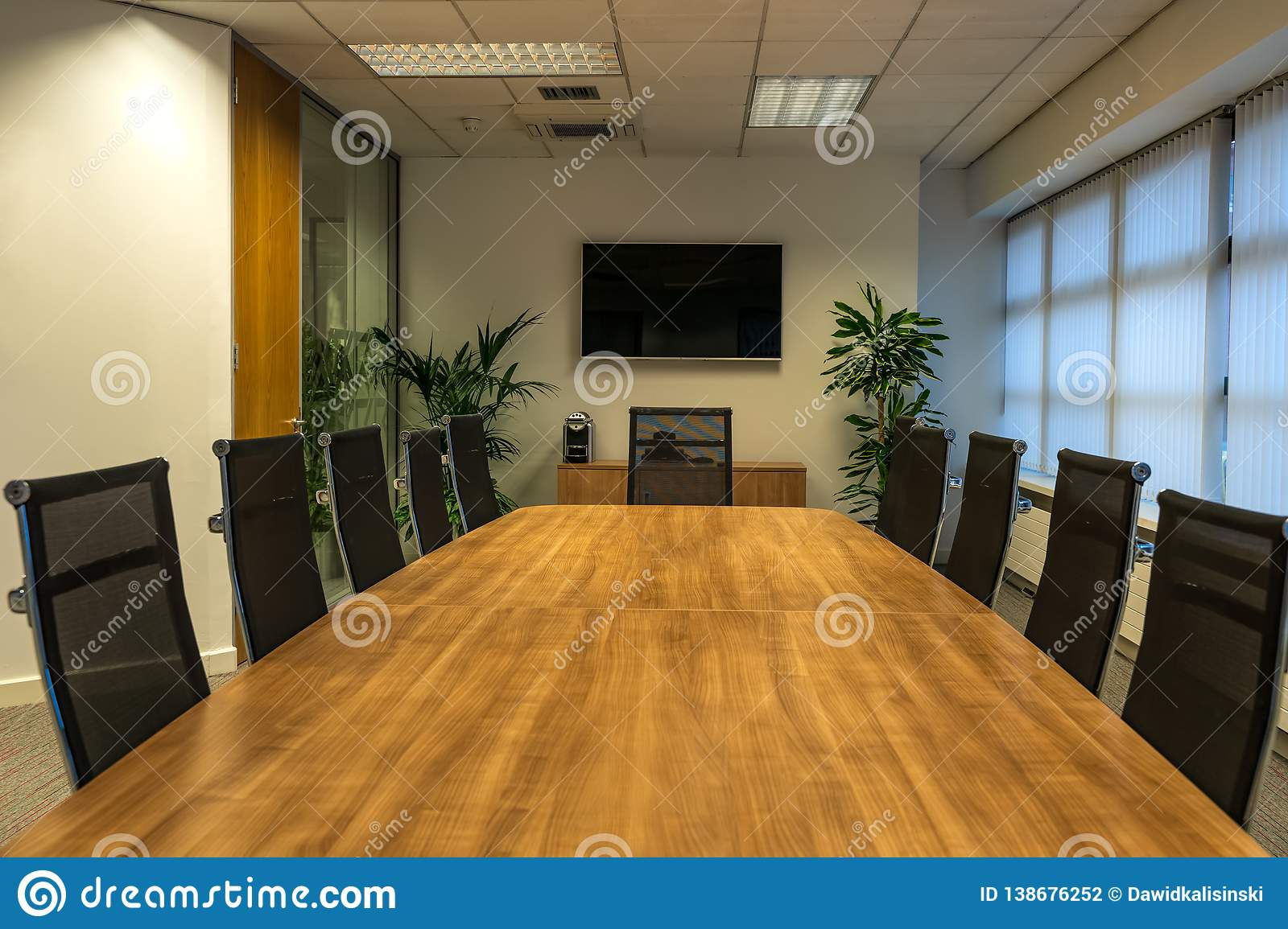 Modern interior of boardroom, meeting or seminar room with chairs and long wooden table at workplace or office, green plants and T