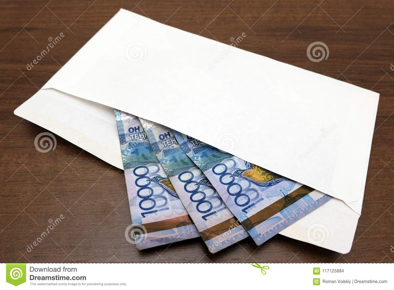 Kazkh money banknotes in a white envelope lie on the table. Thirty thousand tenge are prepared for a gift or a bribe. The concept