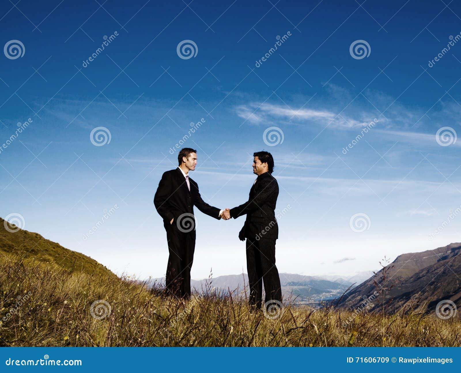 Concept d accomplissement de chaîne de montagne de poignée de main d hommes d affaires