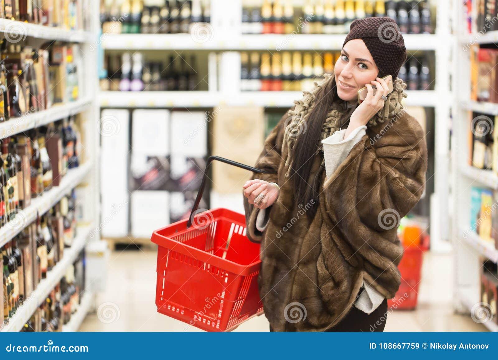 Concept d achats Téléphone parlant de femme et tenir le panier à provisions rouge dans le magasin de supermarché près des fenêtre