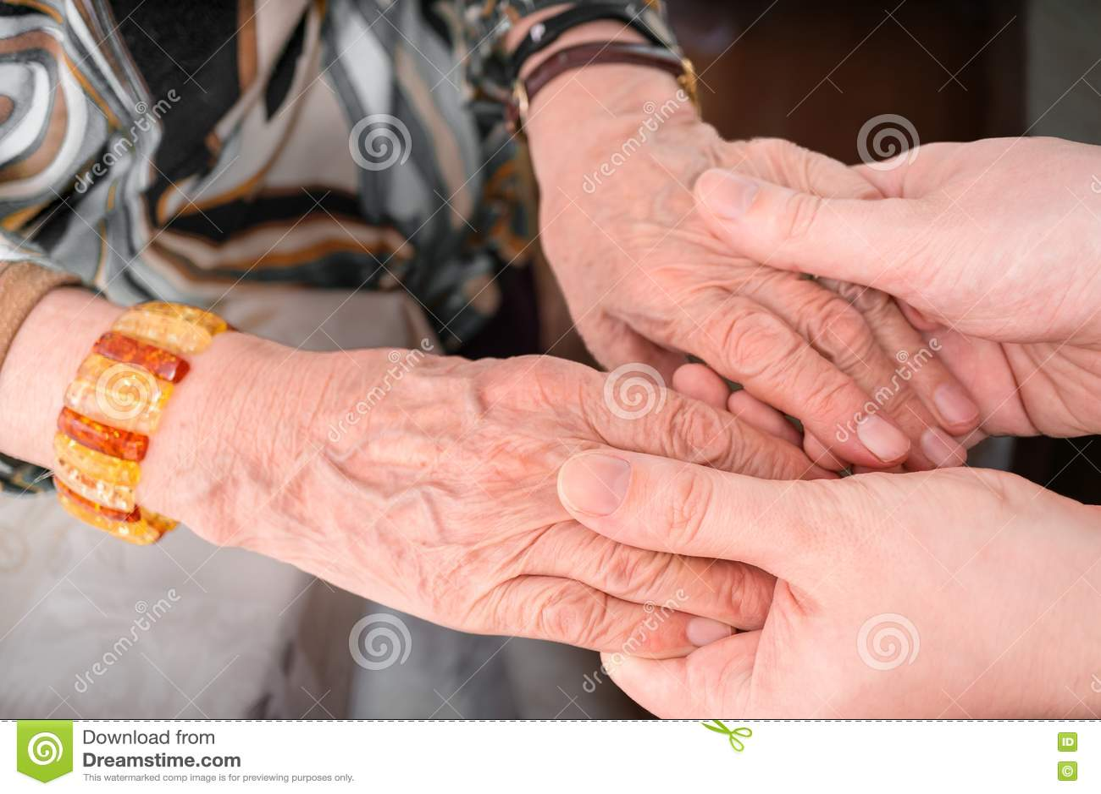 Concept d aide d aîné ou d eldery Le jeune homme tient des mains de femme supérieure