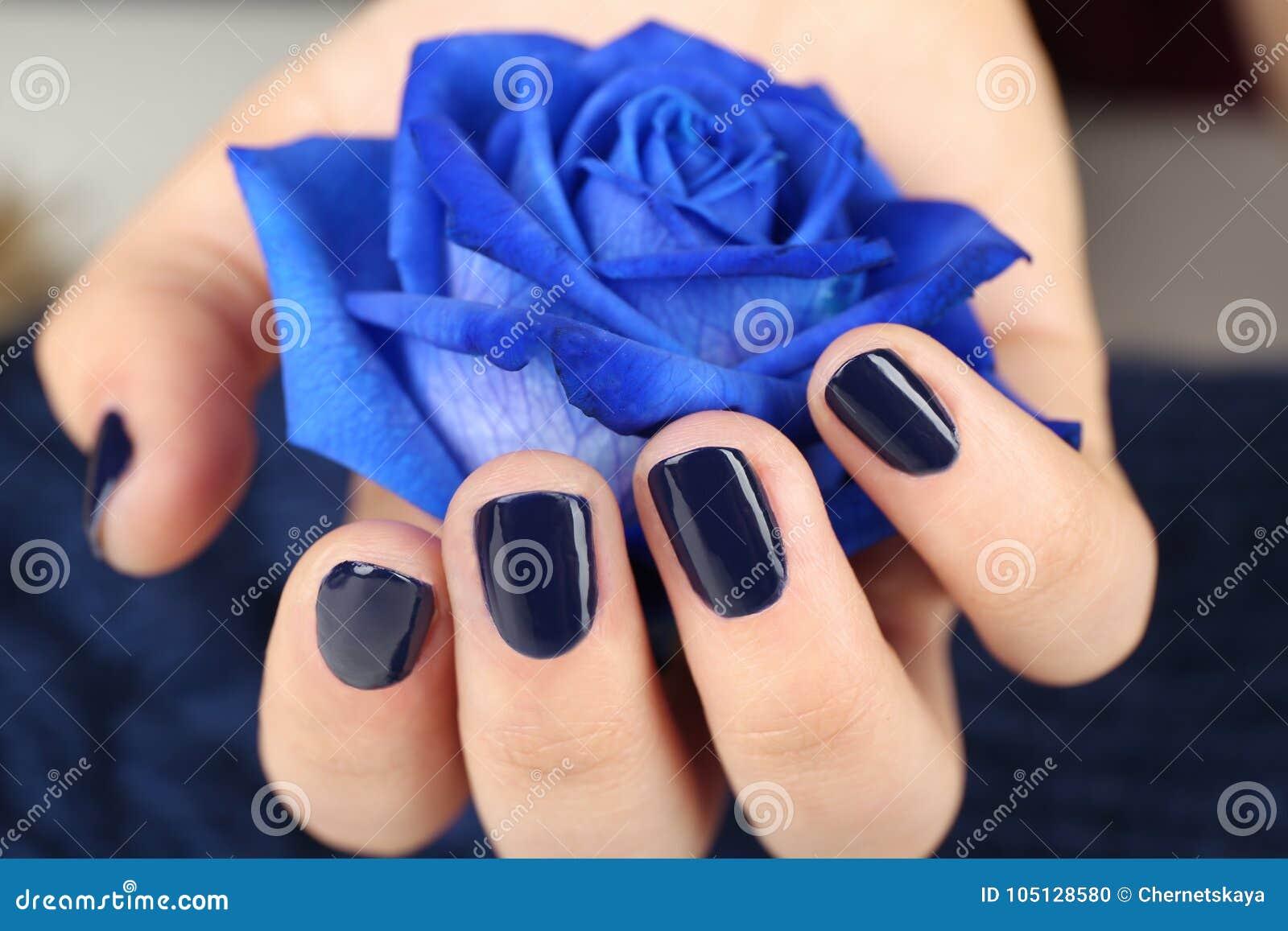 Concept d art de clou Belle main femelle tenant la rose de bleu