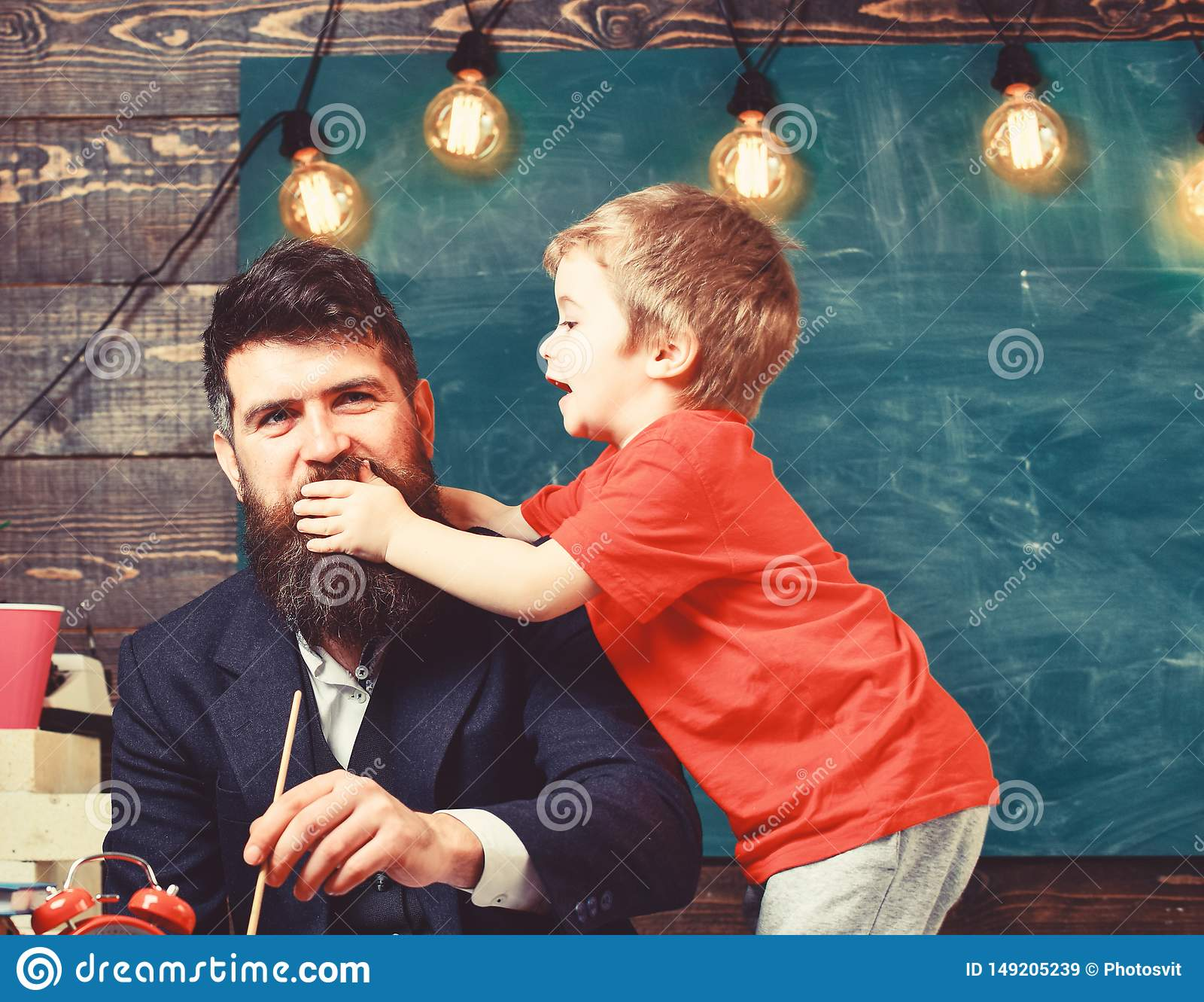 Concept d enfance Peinture de p?re tandis que le fils le distrait Peu d enfant tenant sa main au-dessus de bouche du papa s