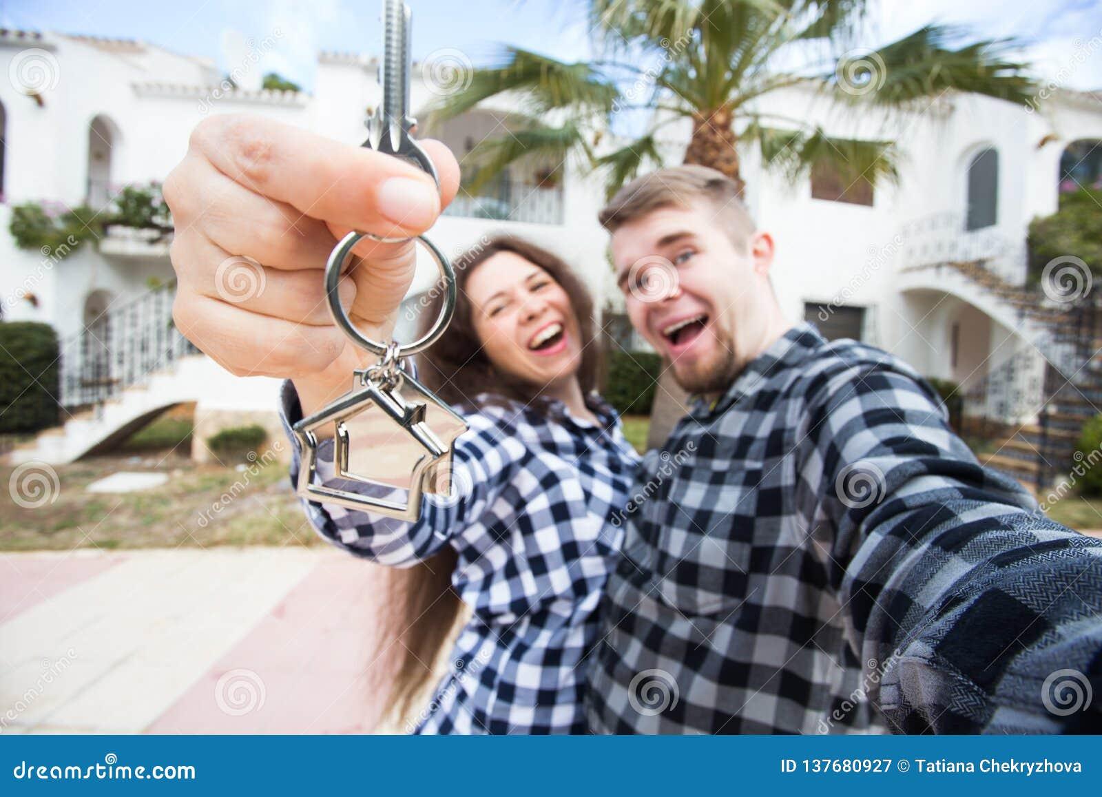 Concept d immobiliers et de propriété - couple heureux tenant des clés sur la nouvelle miniature de maison et de maison