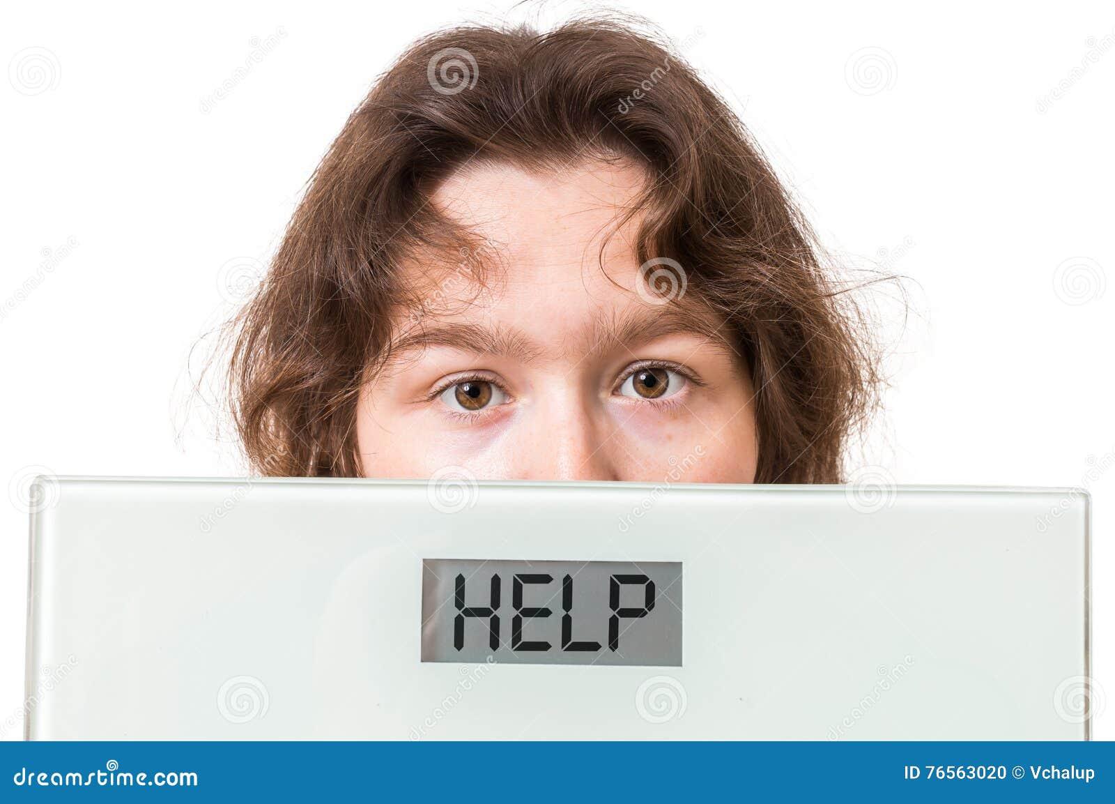 Concept d obésité Échelles de poids excessif de prises de femme avec l aide écrite