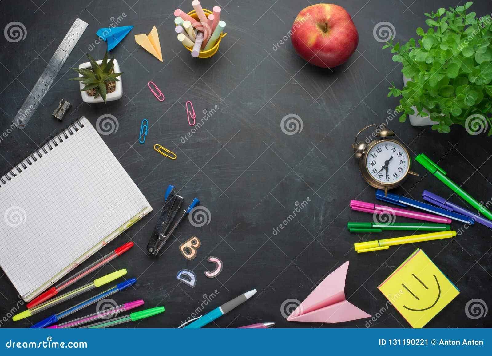 Concept de bannière de nouveau au réveil d école, papeterie de carnet d Apple de crayon sur le fond de tableau noir Accessorie de