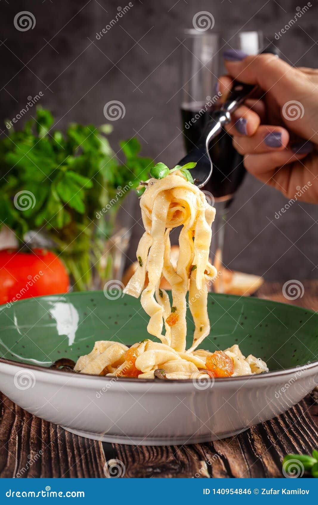 Concept de cuisine italienne Tagliatelles avec des légumes, des tomates, des olives et le parmesan Décoré du persil portion