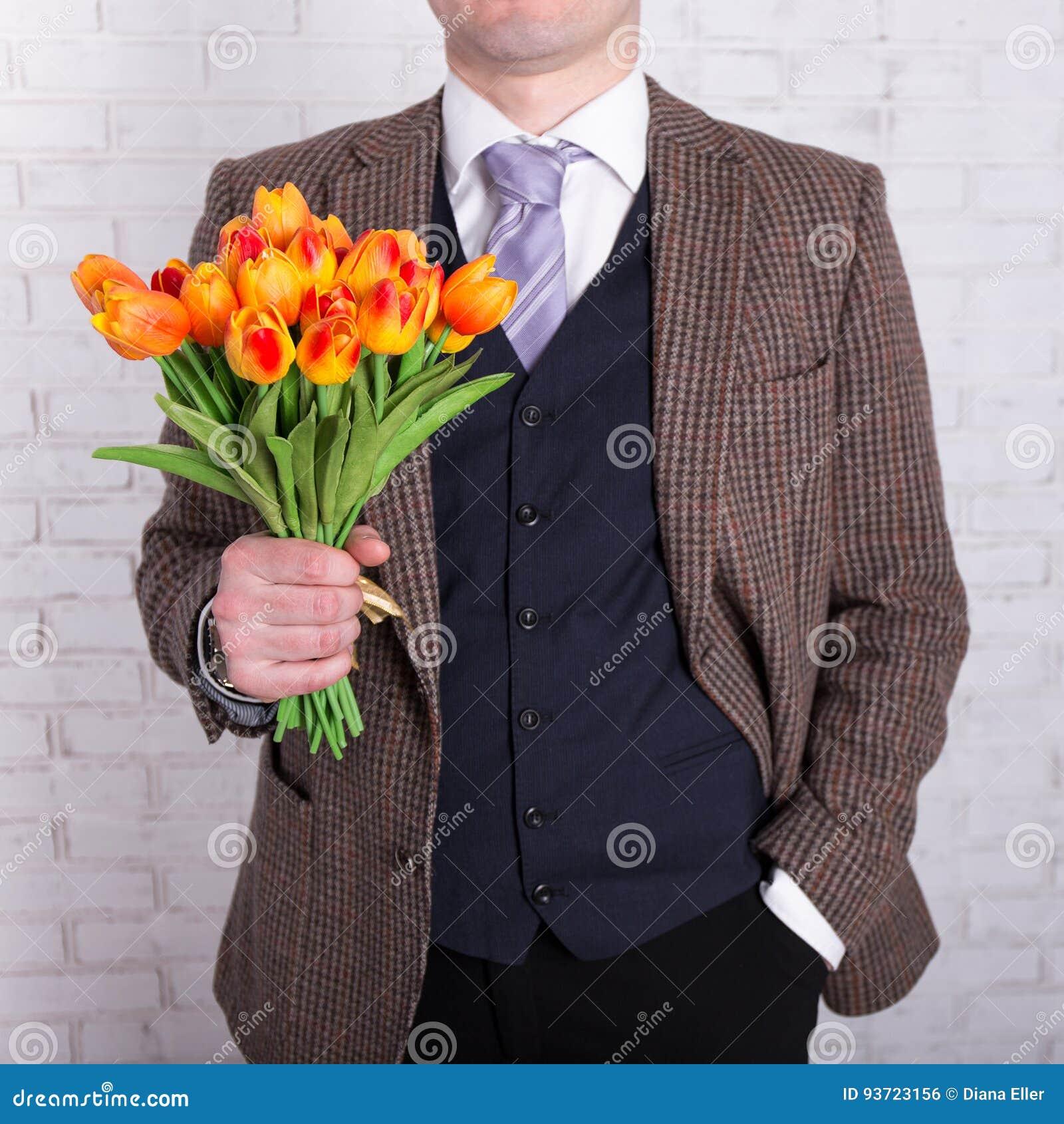 Concept de datation - fermez-vous des fleurs dans des mains masculines