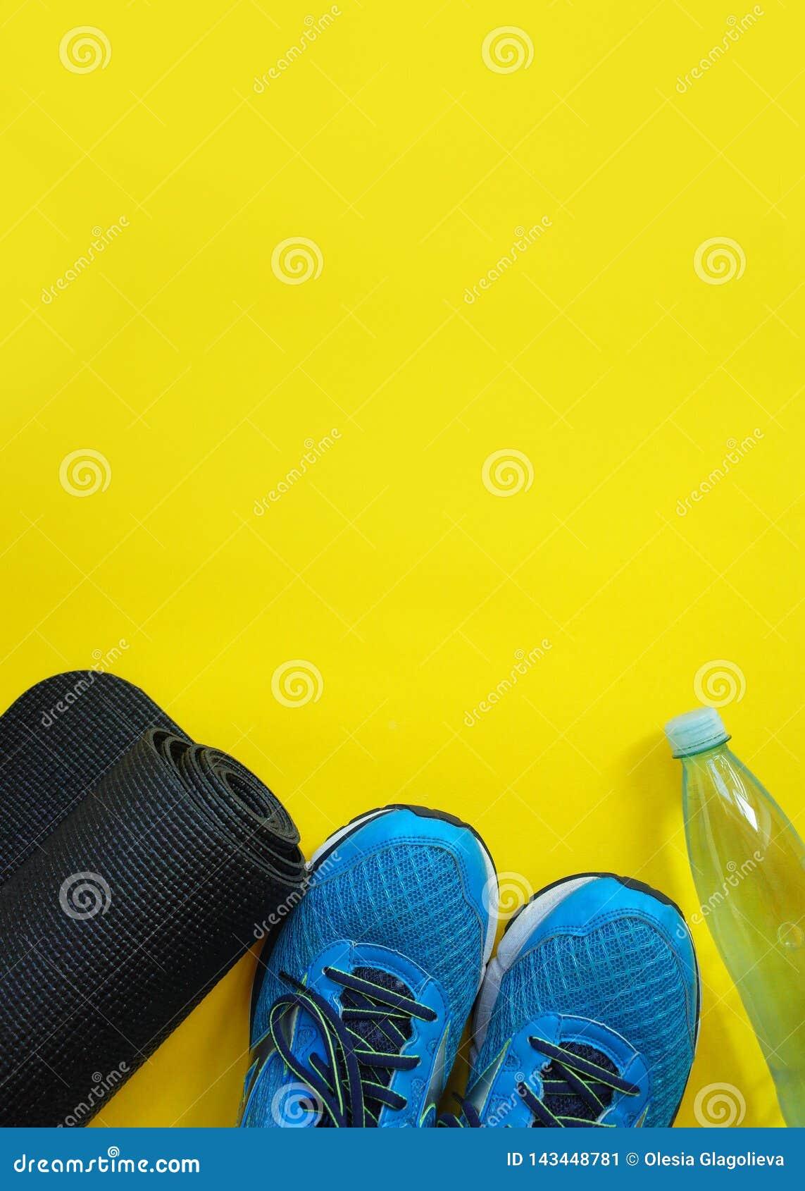 Concept de forme physique, sain et actif de modes de vie, chaussures de sport, bouteille des eaux, tapis sur le fond jaune Copiez