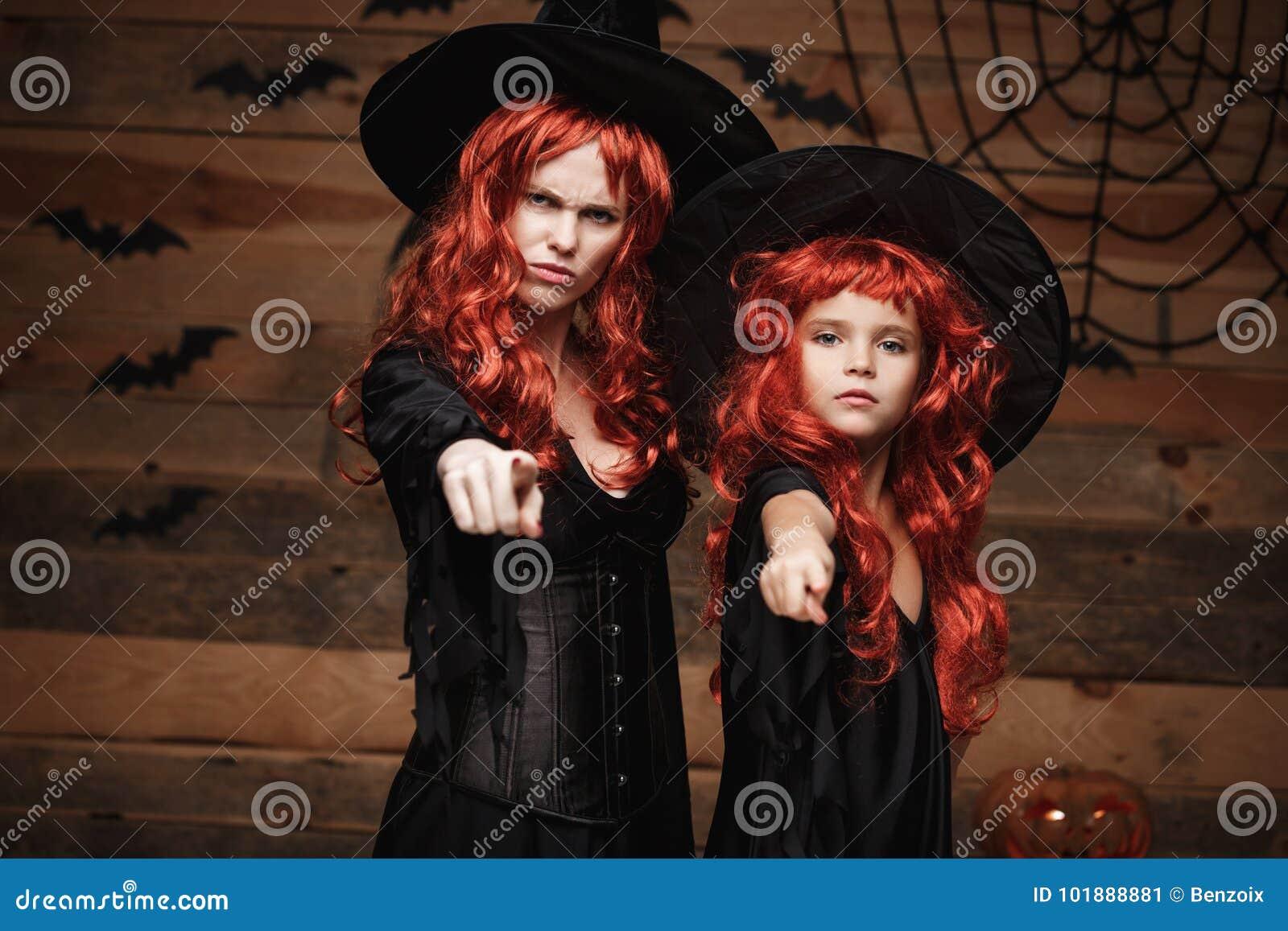 Concept de Halloween - belle mère caucasienne et sa fille avec de longs cheveux rouges dans des costumes de sorcière avec l expre