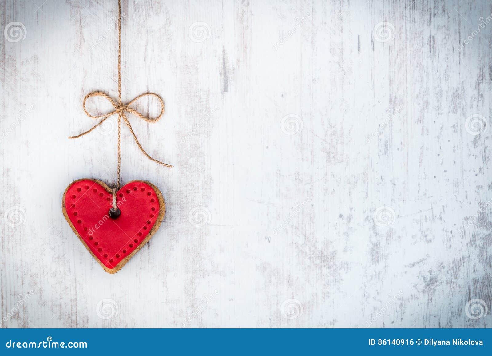 Concept de jour de Valentines Biscuit en forme de coeur attaché avec l arc de chanvre au-dessus du fond rustique en bois blanc