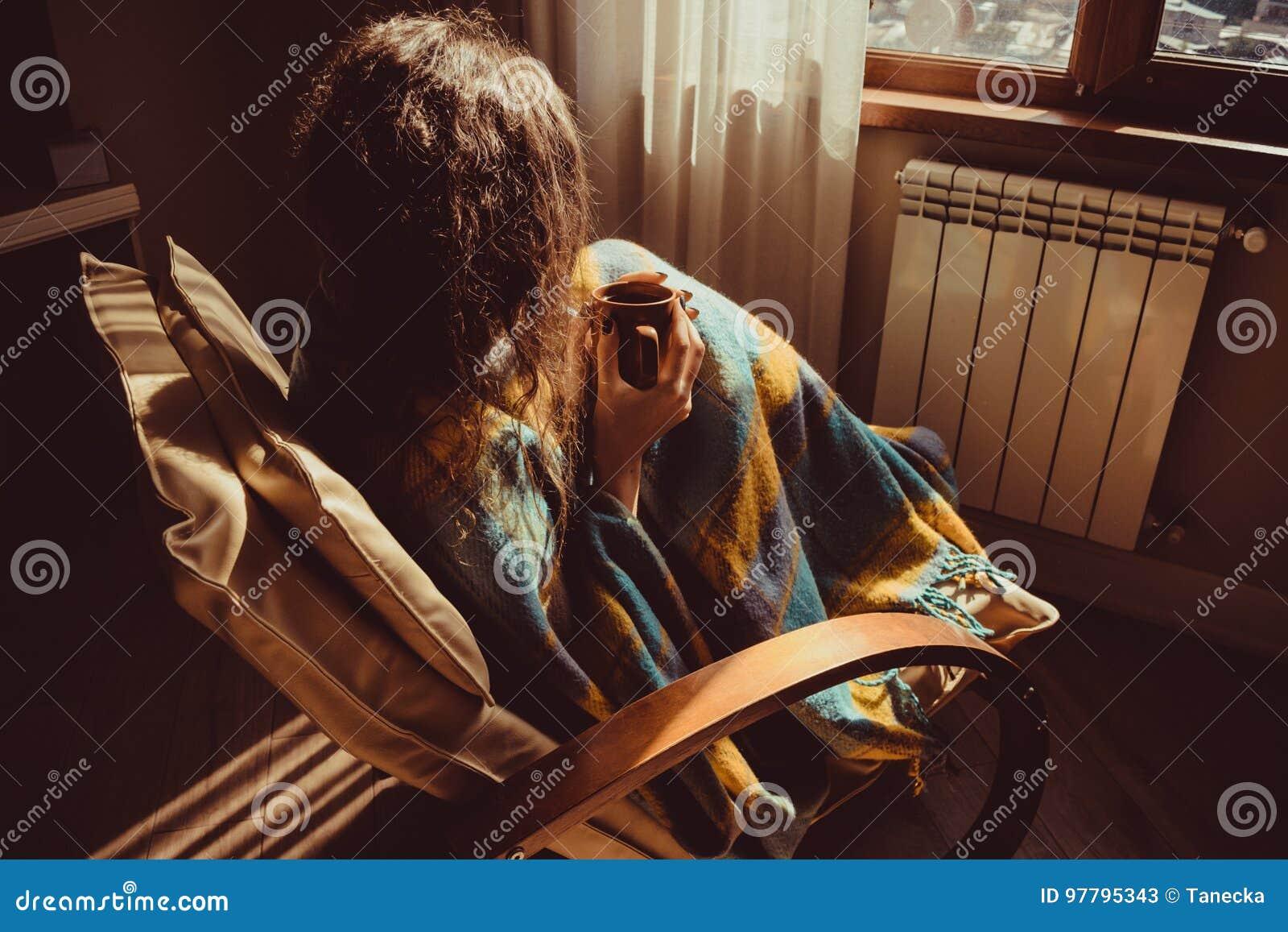 Concept de l hiver Jeune femme s asseyant dans la chaise moderne confortable près du radiateur avec la tasse de thé enveloppée da