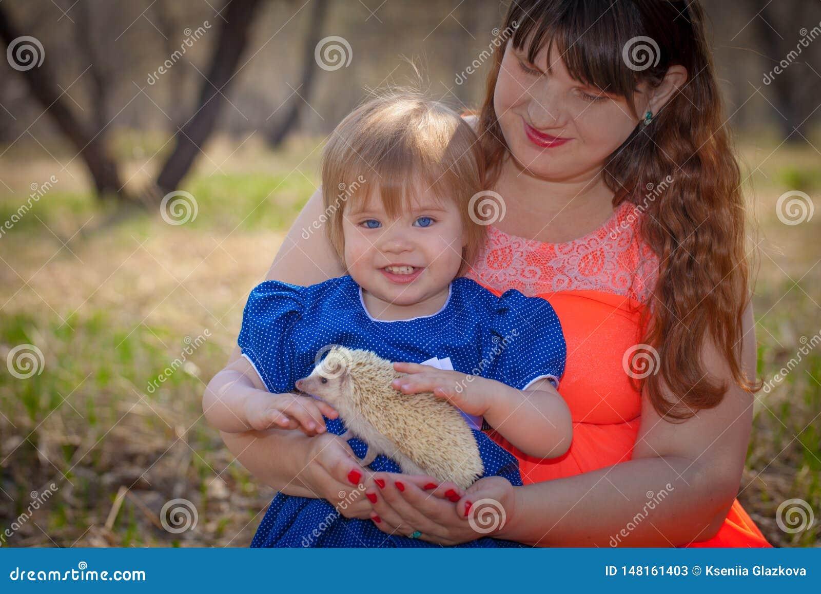 Concept de la famille La maman et la fille jouent avec un h?risson