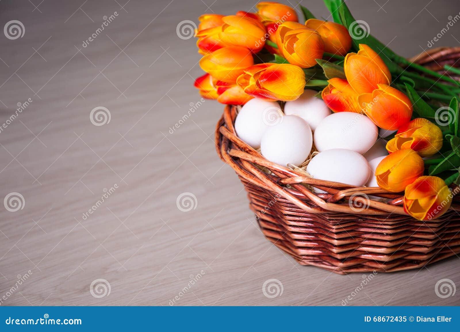 Concept de Pâques - oeufs blancs et tulipes dans le panier sur la table en bois