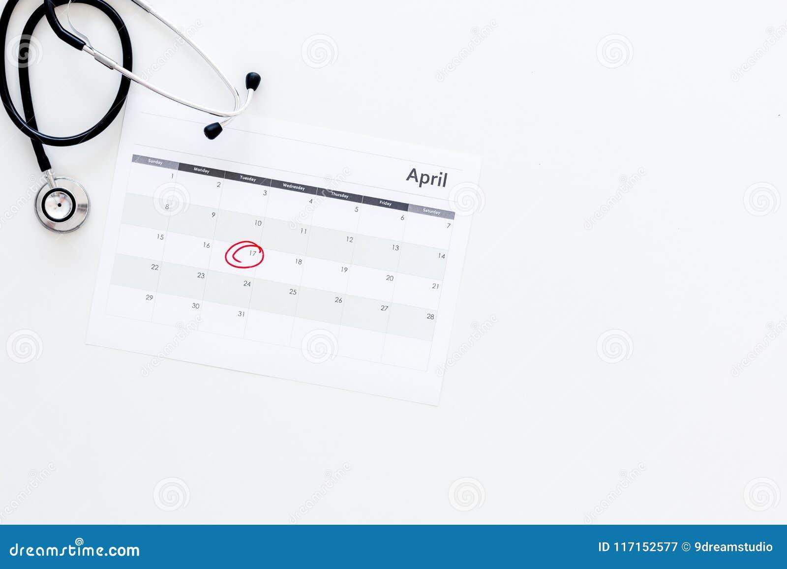 Concept de planification d examen médical Examens médicaux réguliers Calendrier avec la date cerclée et stéthoscope sur le blanc