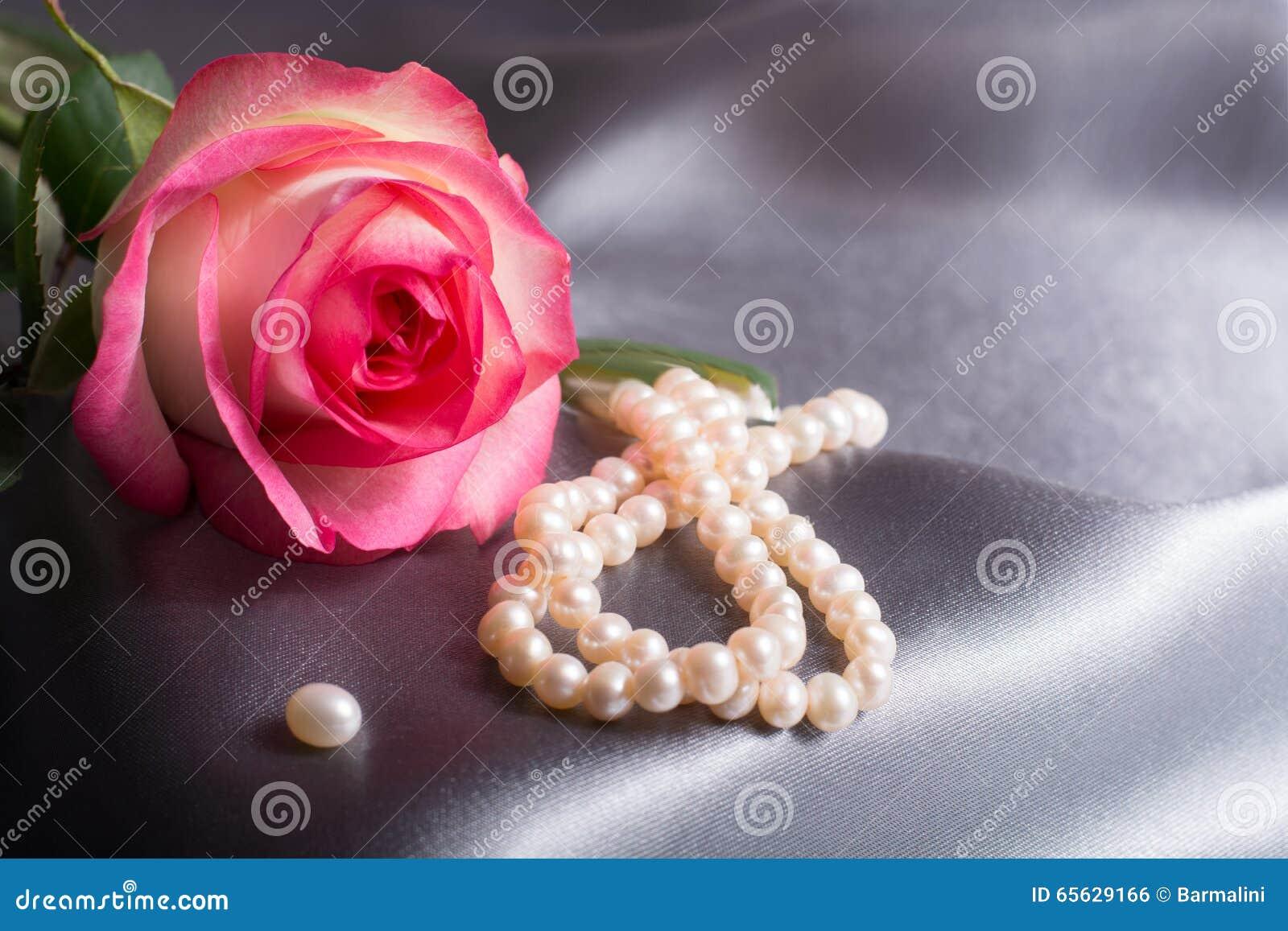 Concept de Saint-Valentin, concept de fête des mères, rose de rose sur le fond gris en soie avec des perles