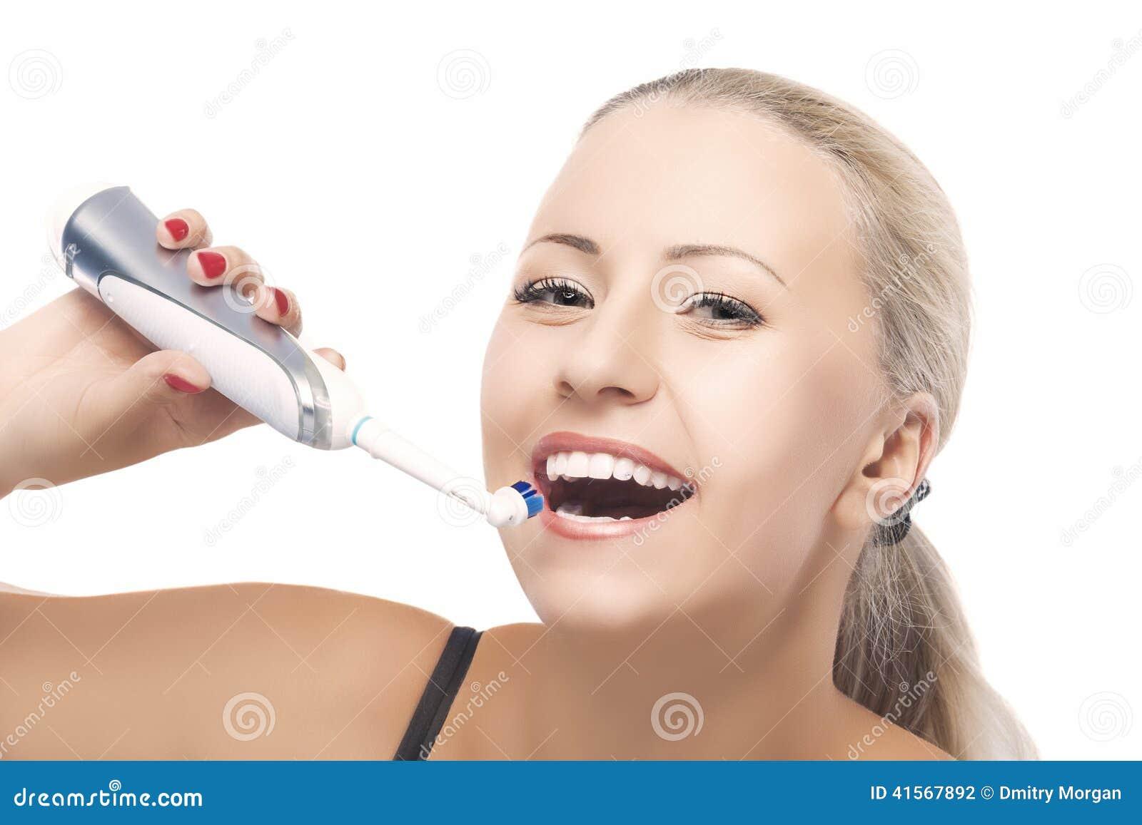 Concept de santé dentaire : Femme caucasienne blonde balayant sa pièce en t