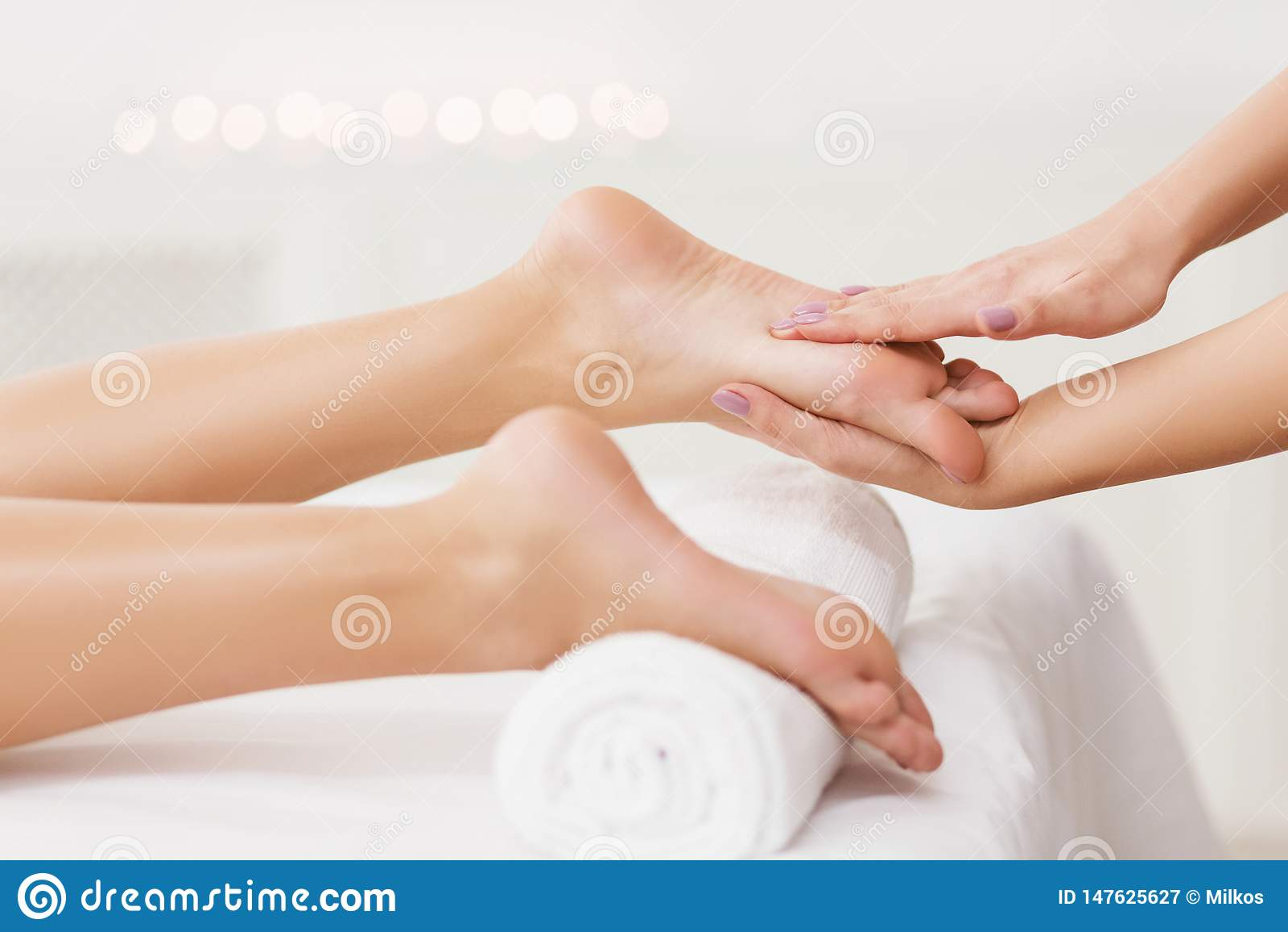 Concept de station thermale Masseur massant le plan rapproché femelle de pieds