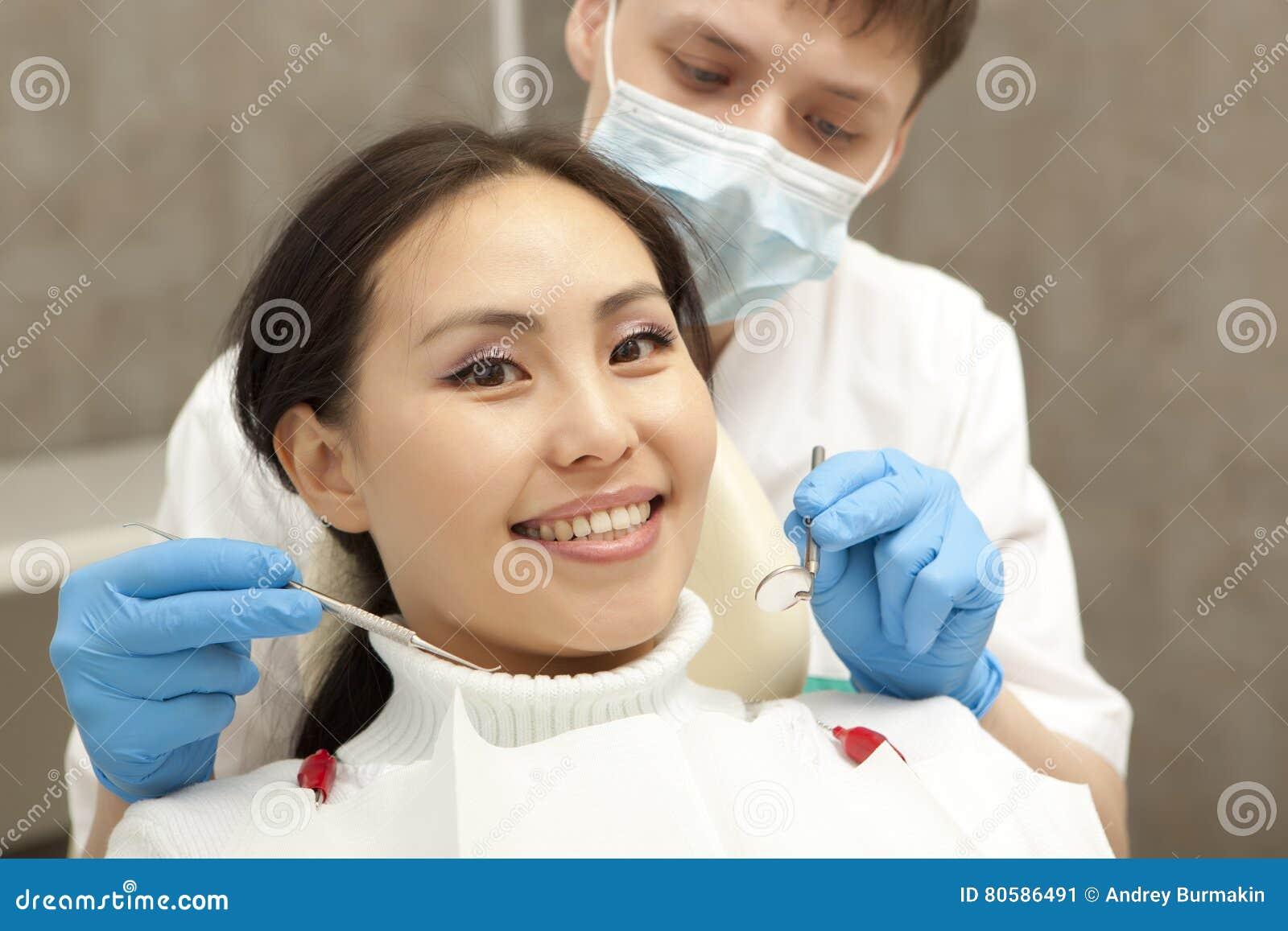 Concept de stomatologie - dentiste masculin avec le miroir vérifiant le patient