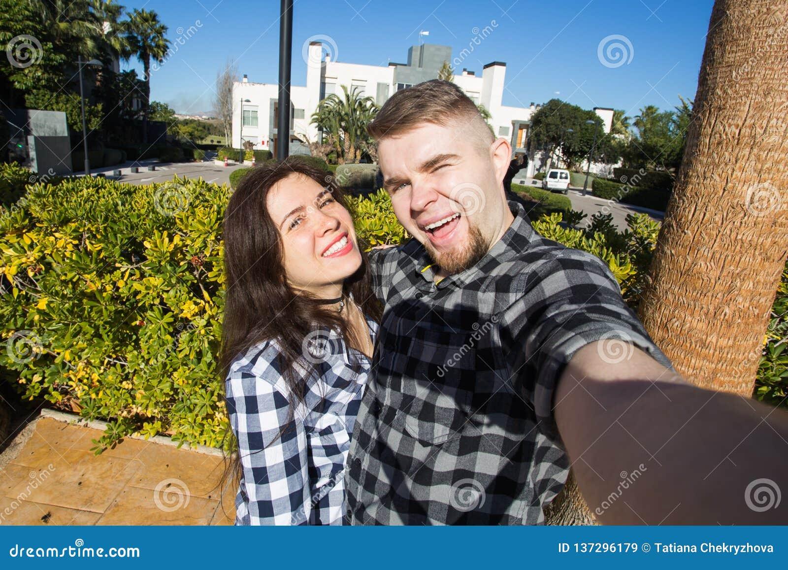 Concept de voyage, de vacances et de vacances - couple drôle heureux prenant le selfie sur la rue