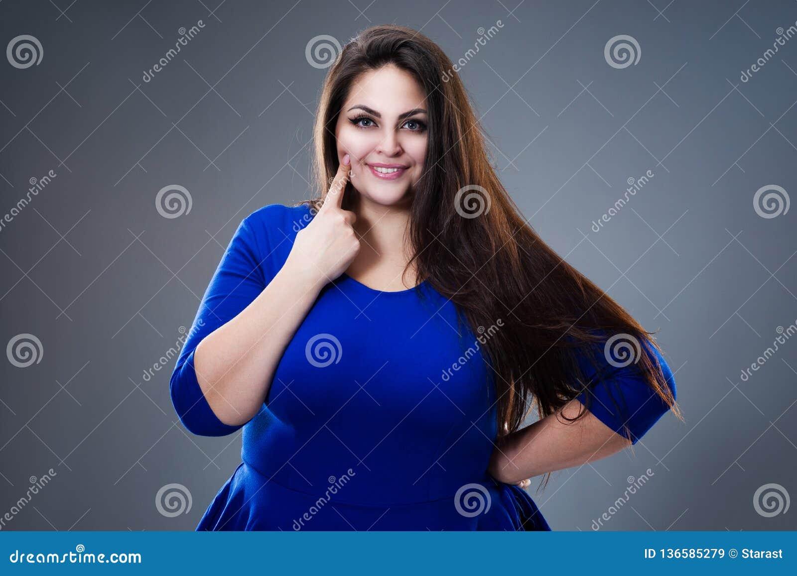 Concept dentaire de santé, grosse femme indiquant ses dents, plus le modèle de taille dans la robe bleue sur le fond gris