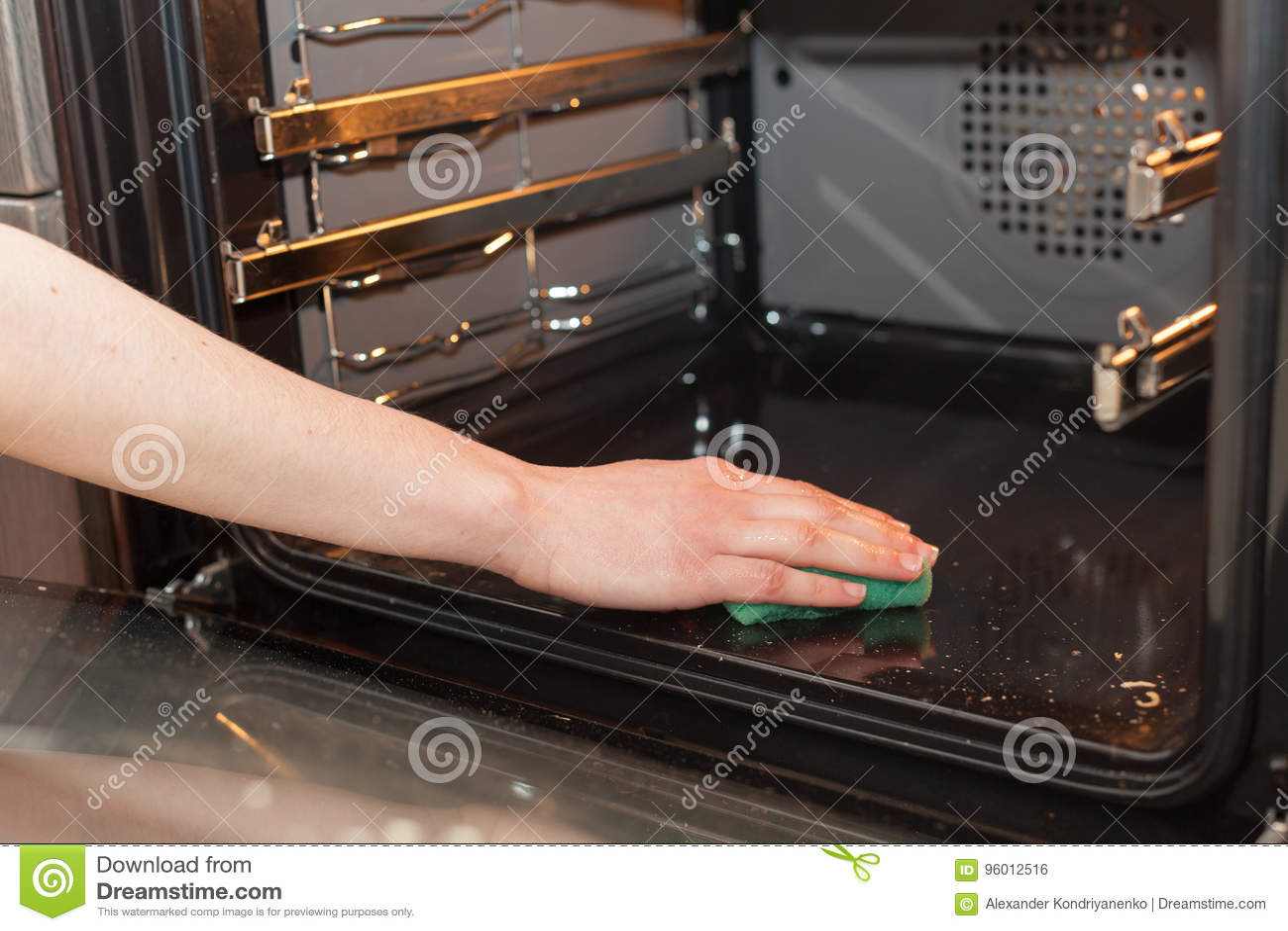 Concept des travaux domestiques et de ménage Frottement du fourneau et du four Main femelle avec l éponge verte nettoyant le four