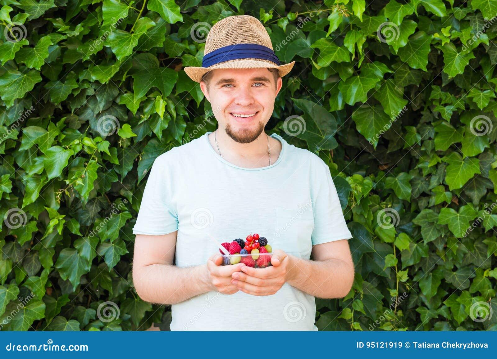 Concept des végétariens, de la nourriture crue et des régimes - la prise belle d homme porte des fruits et des baies