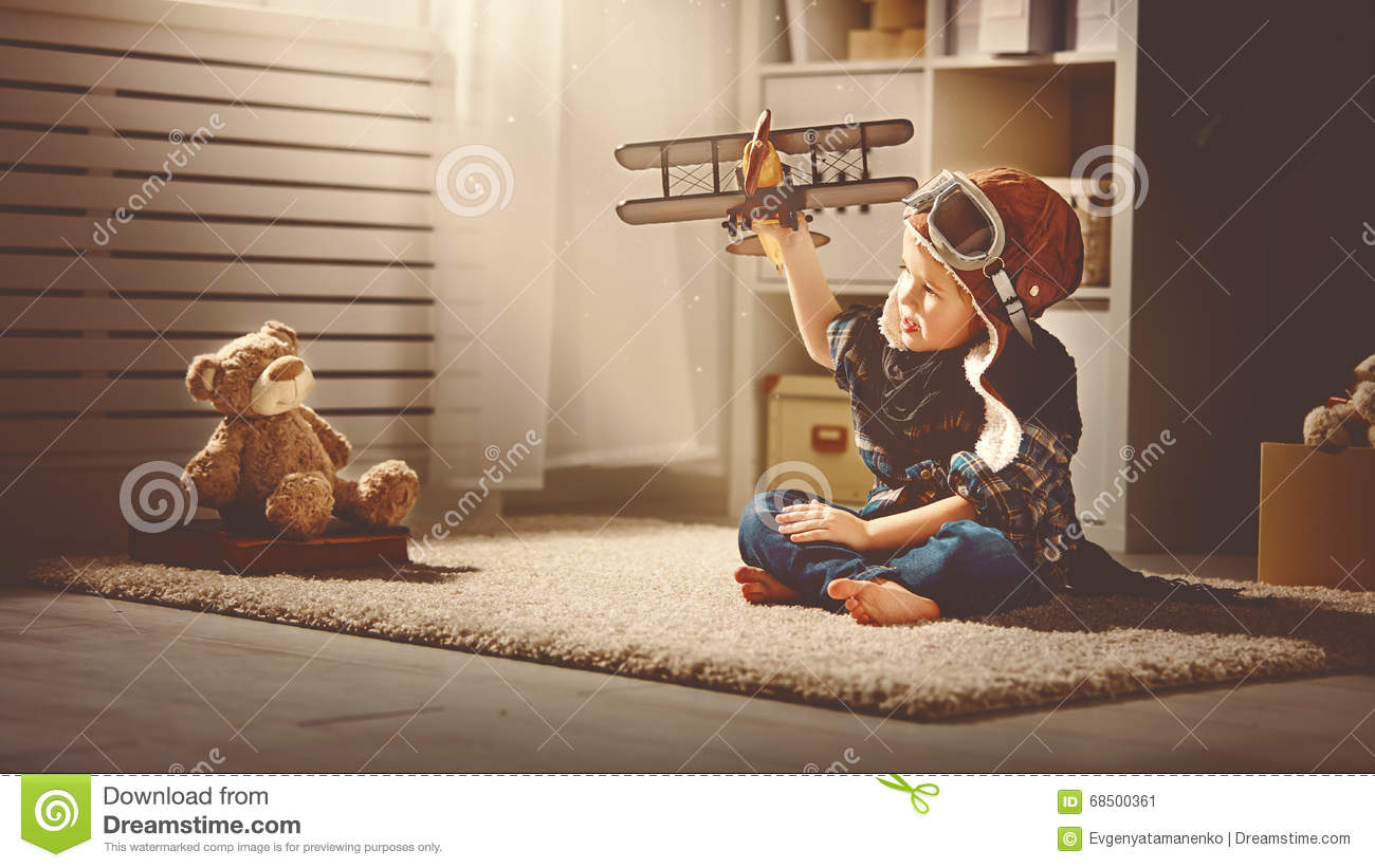 Concept of dreams and travels. pilot aviator child with a toy a