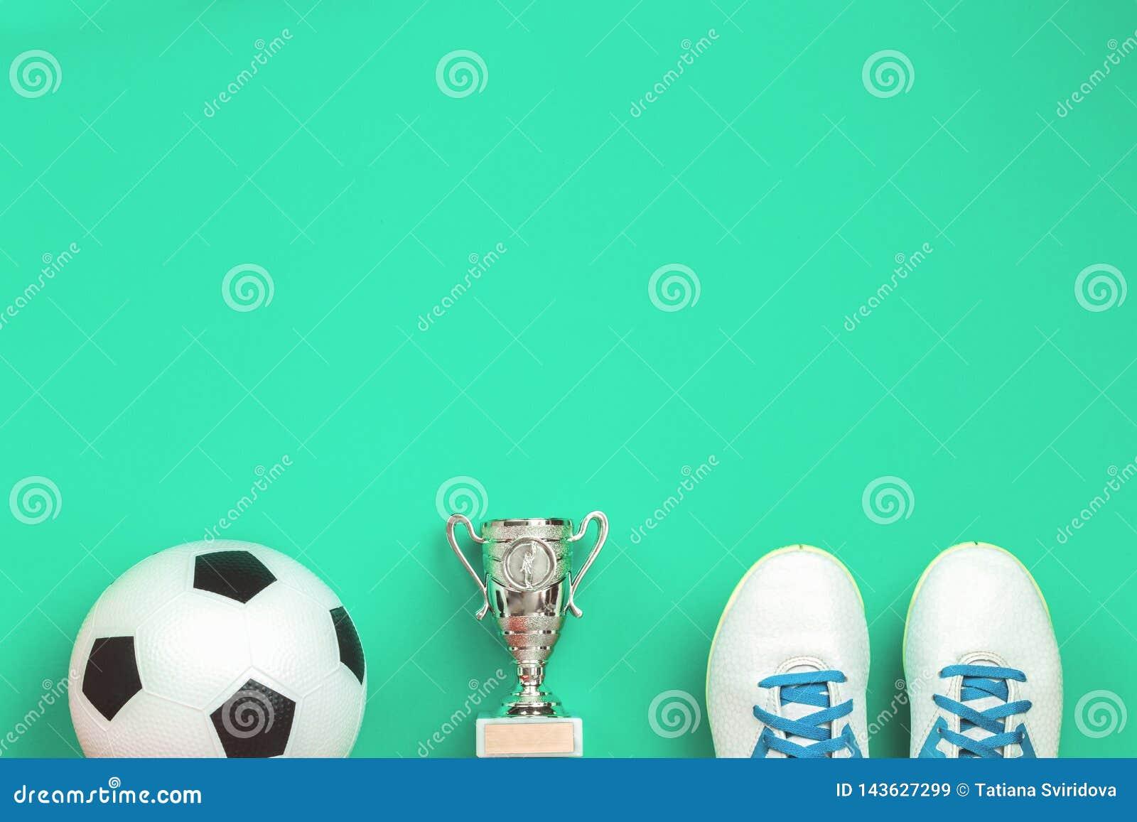 Concept du football avec les chaussures, la tasse et la boule du football