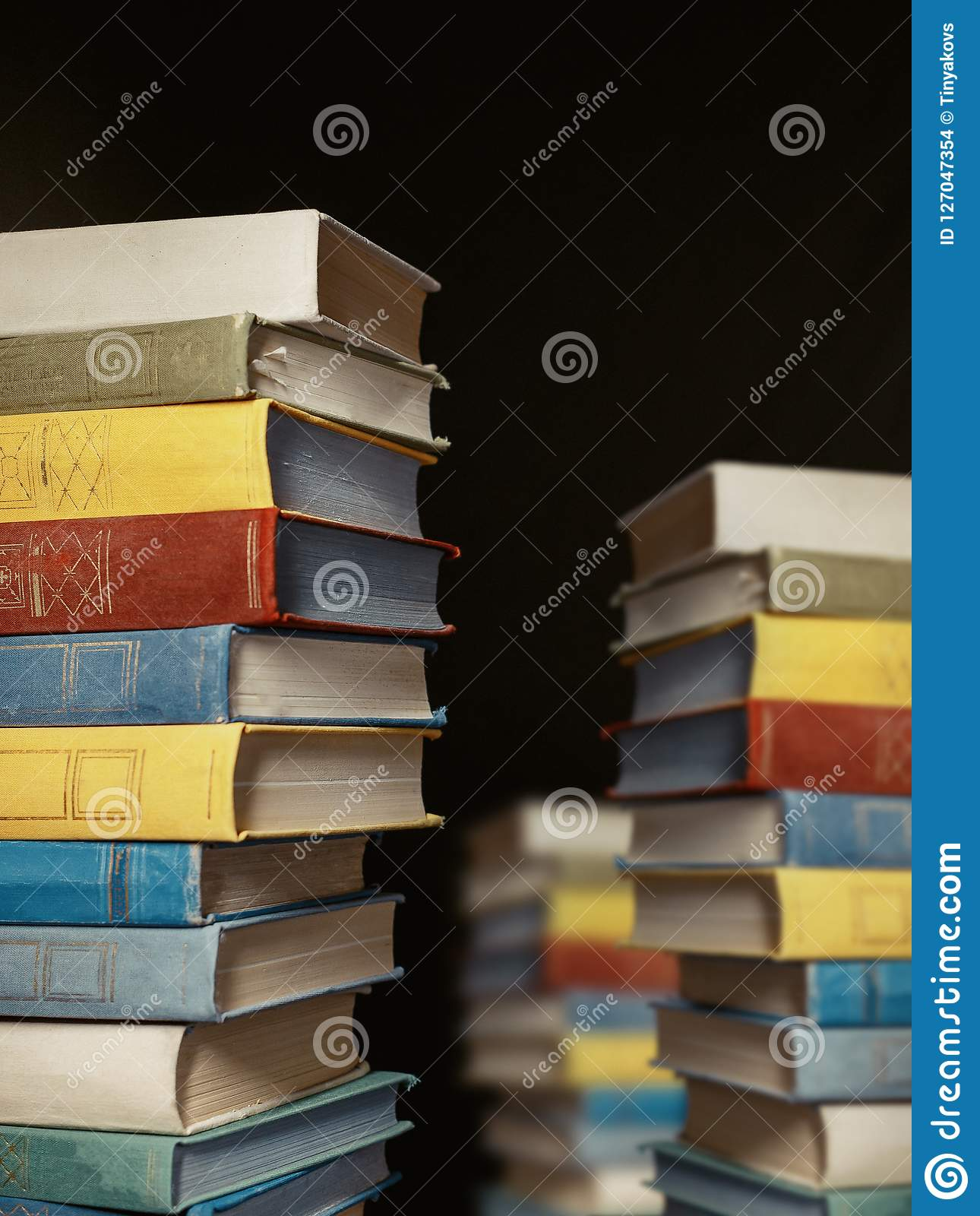 Concept Of Education And Knowledge. Tower Building Of Old Colorful Books On Black Background