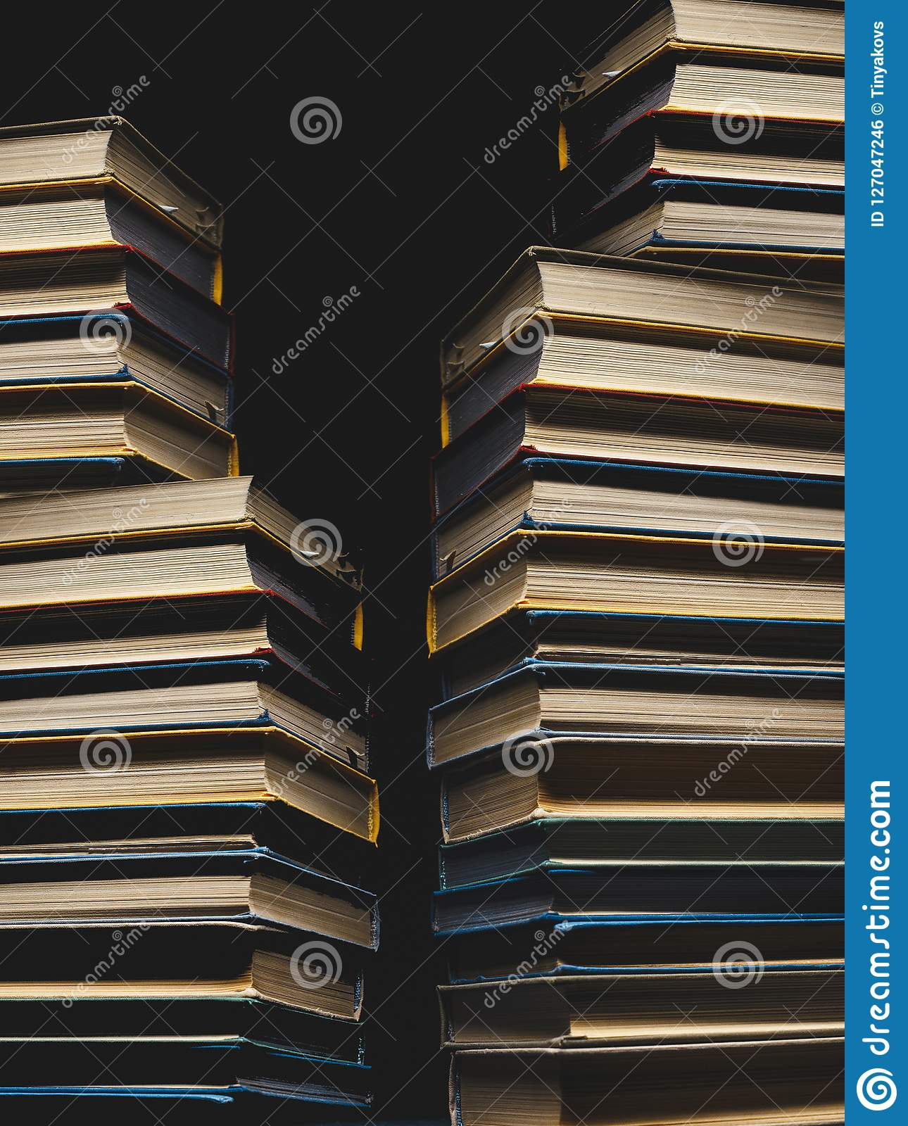 Concept Of Education And Knowledge. Tower Building Of Old Multicolored Books On A Black Background