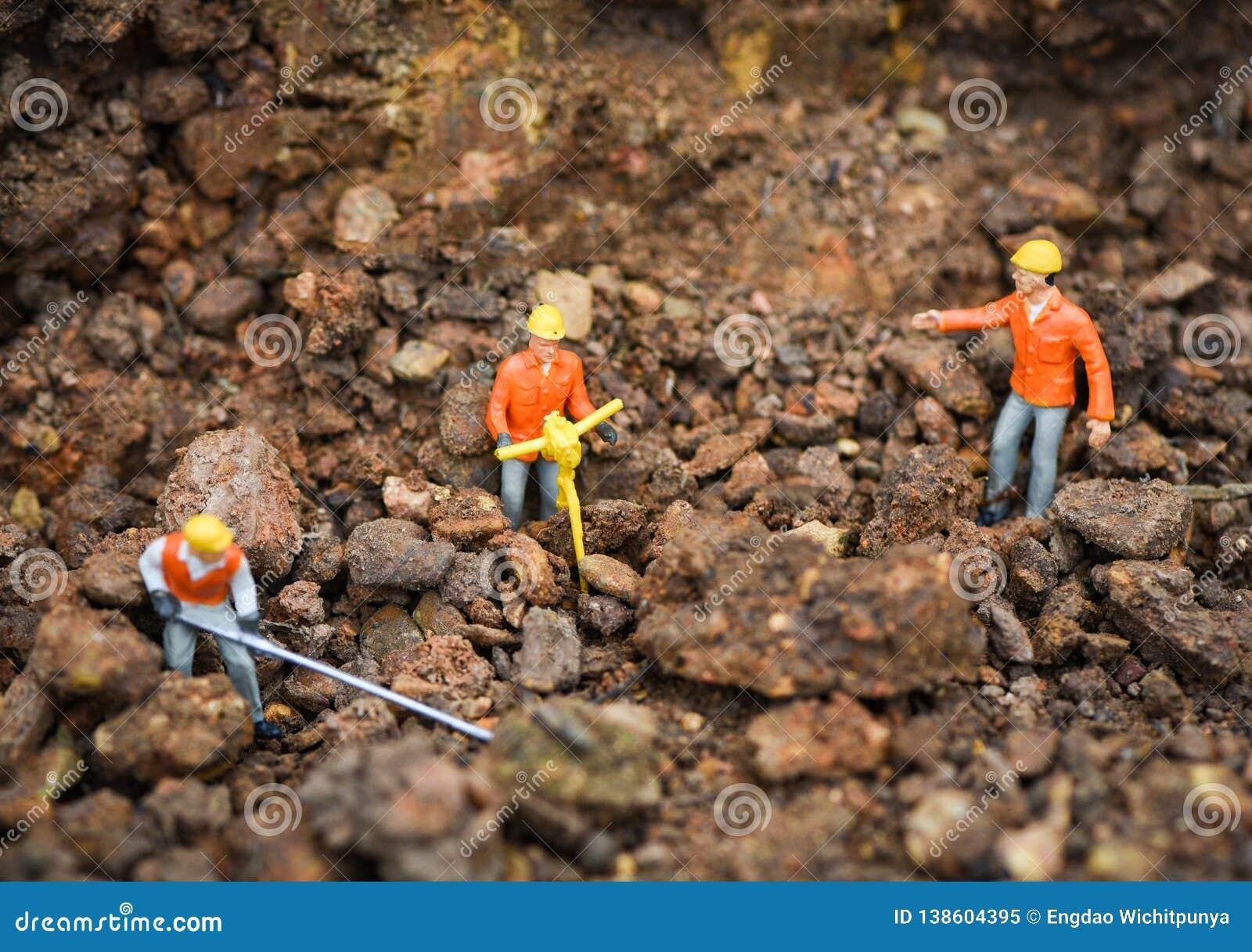 Concept/figurines de travailleur de la construction fonctionnant le sol moulu de creusement avec le regard d ingénieur d équipes
