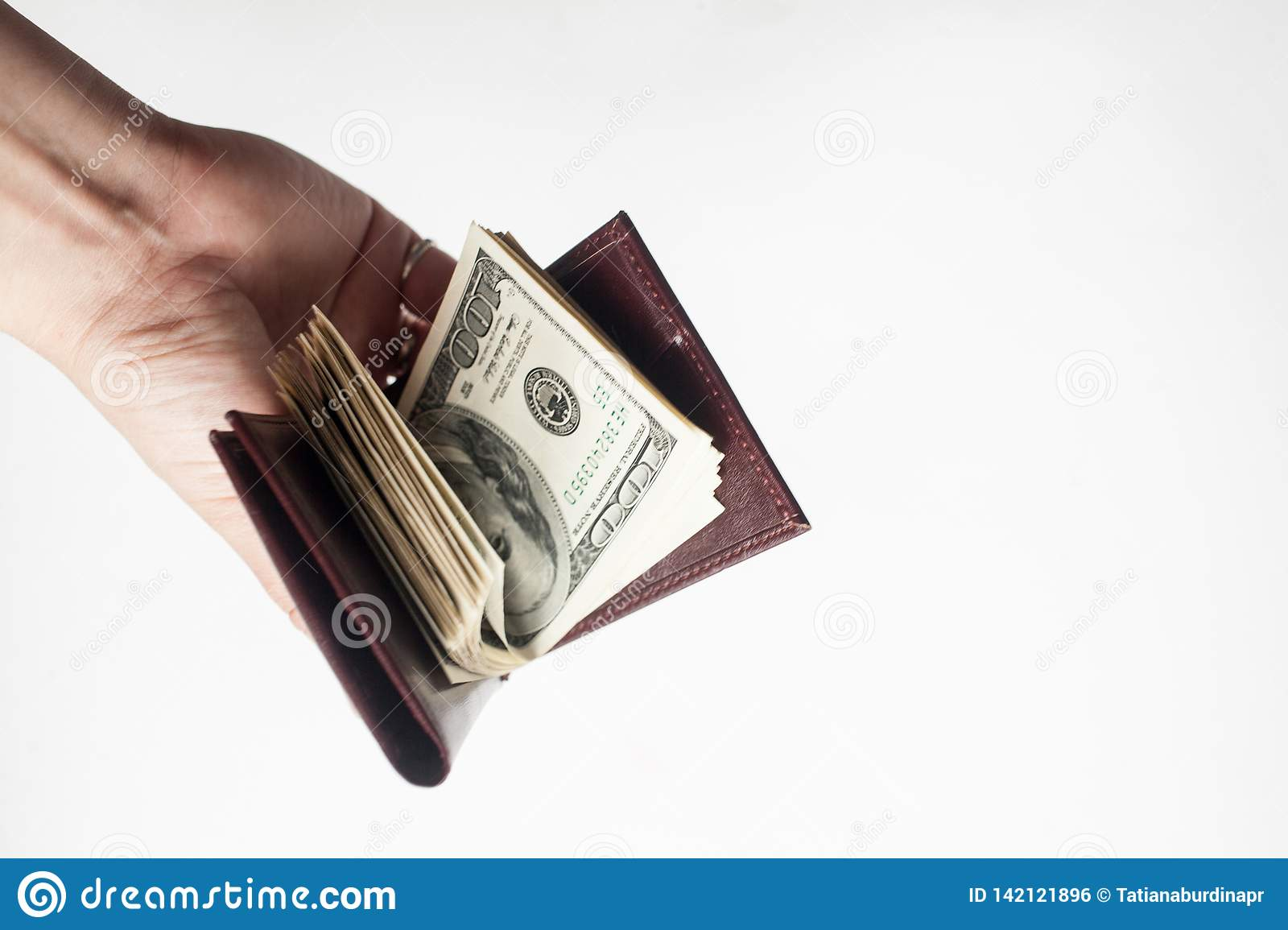A hand holding a wallet full of one hundred dollar bills isolated over a white background