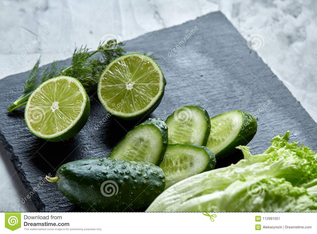 Concept of fresh green lettuce, cucumber, dill, lime on a light background, selective focus, top view, copy space.