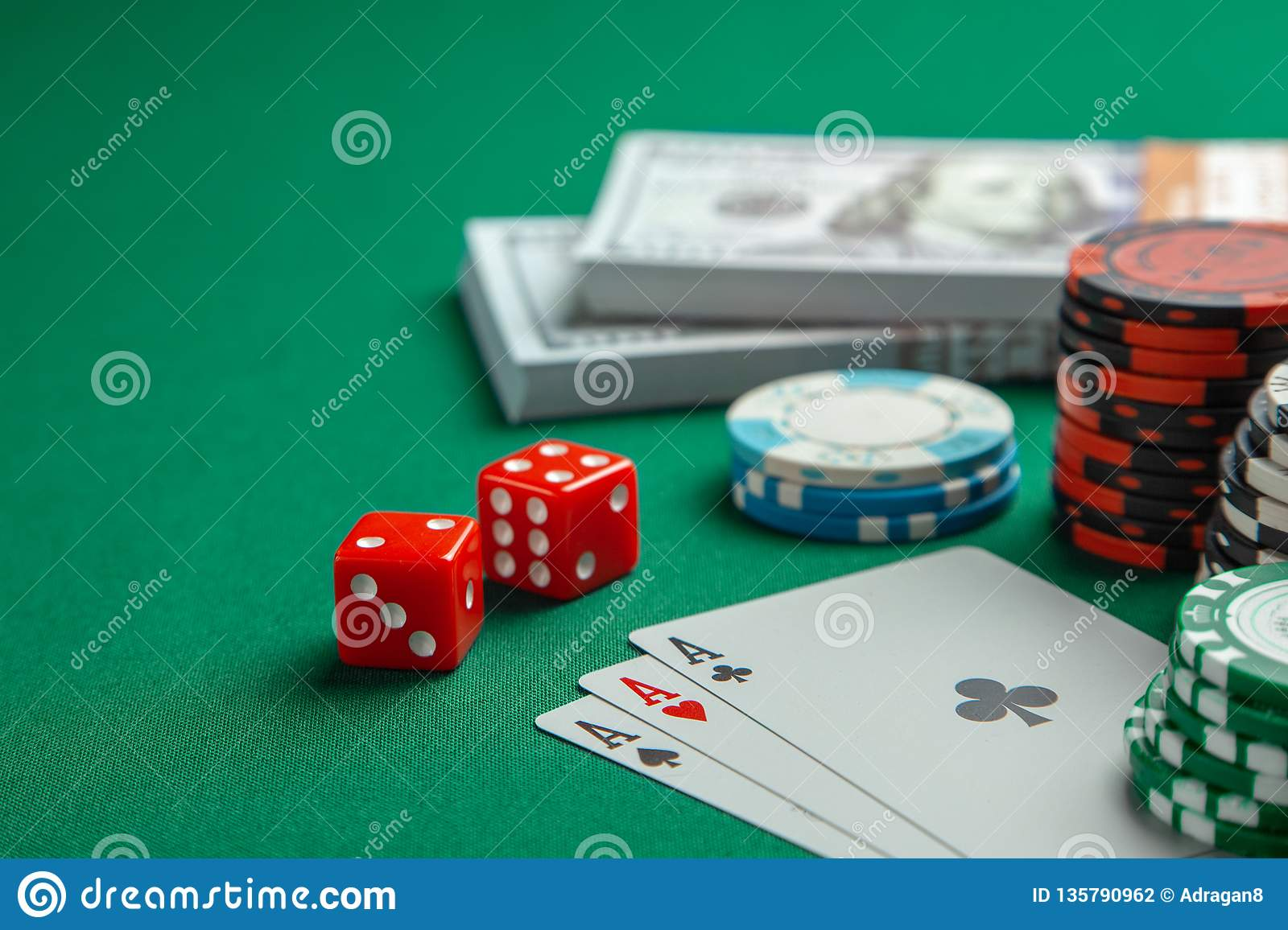 Concept of gambling in casino, sports poker. Playing cards with dice and colored chips with cash money dollars on green table.