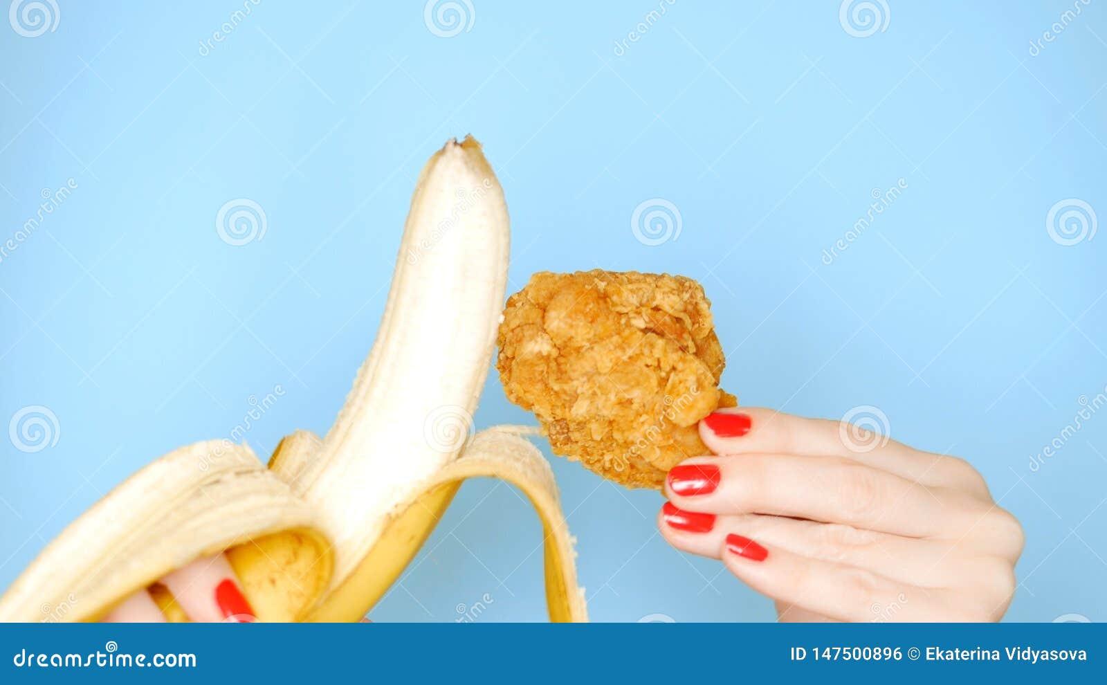 Concept gezond en ongezond voedsel banaan tegen gebraden gepaneerd kippenbeen op een heldere blauwe achtergrond wijfje