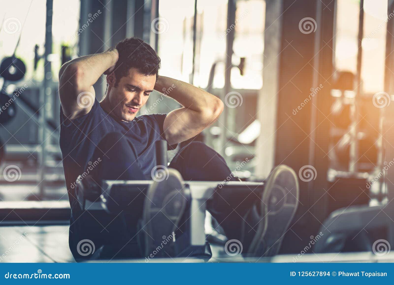 Concept Gymnastiek, Fitness, Gezonde Sport, Levensstijl De geschikte jonge mens zit UPS op machine in sportkleding