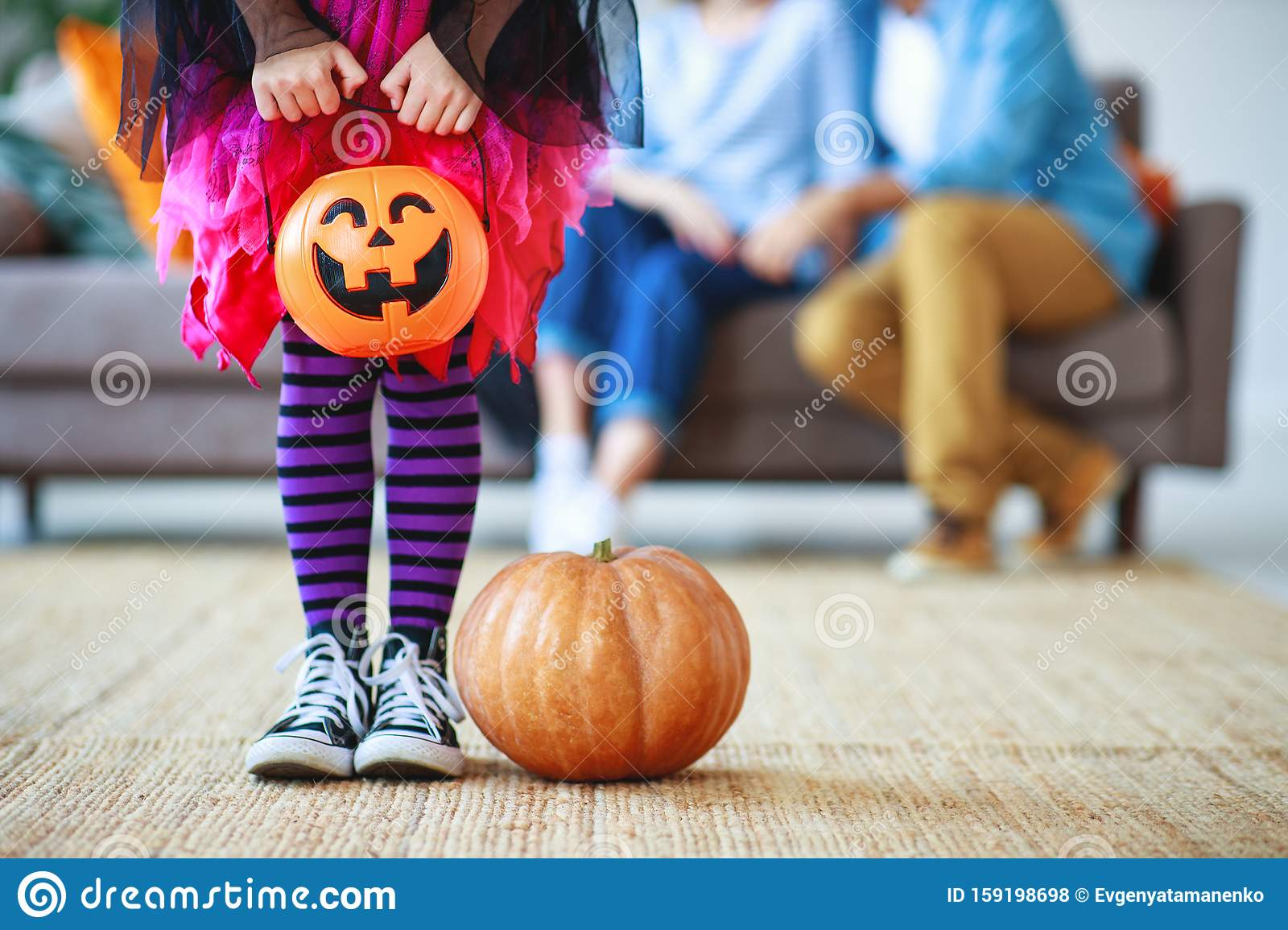 Concept of Halloween. child girl legs in witch costume with pumpkin