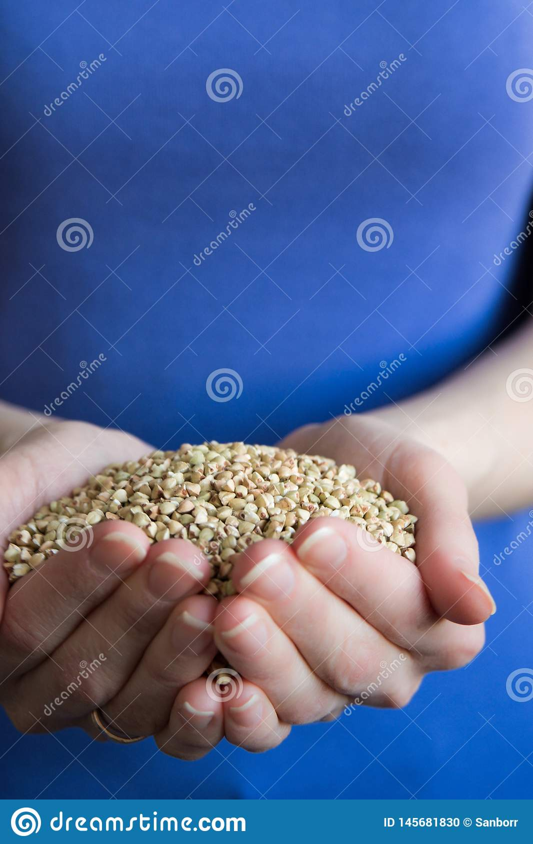 A handful of green buckwheat grain in the hands of a woman top view. The concept of healthy organic food