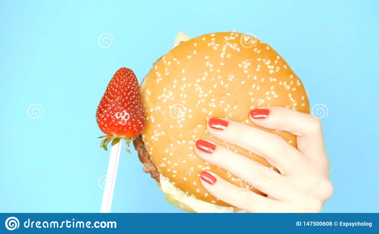 Concept of healthy and unhealthy food. Strawberries against hamburgers on a bright blue background. female hands with