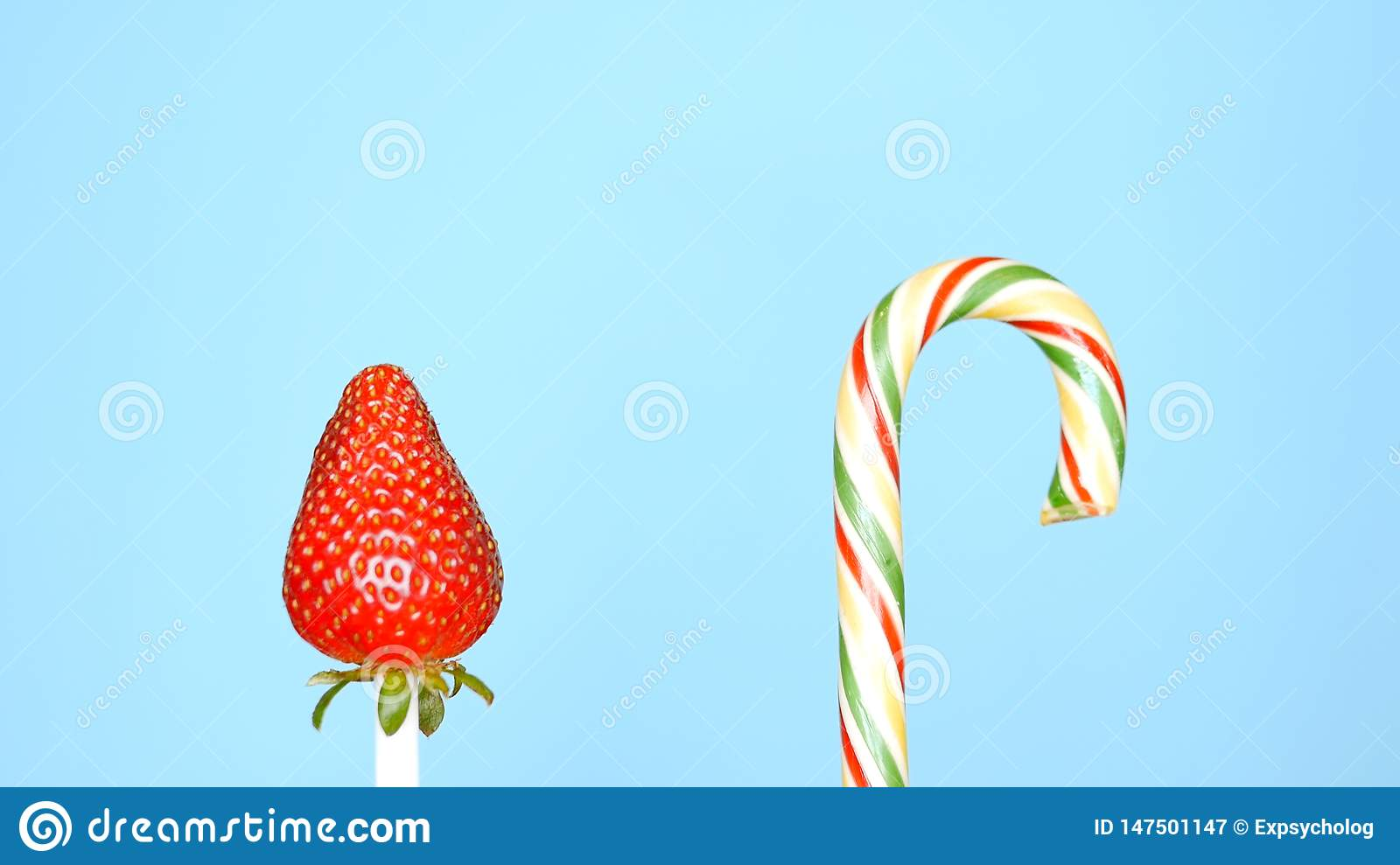 Concept of healthy and unhealthy food. strawberry against candy on a bright blue background