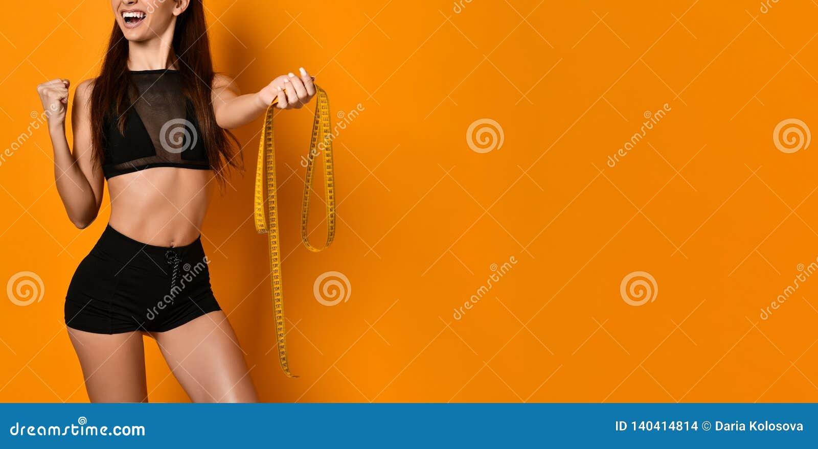 Concept het gezonde eten Jong meisje met perfecte taille met een metende band in handen