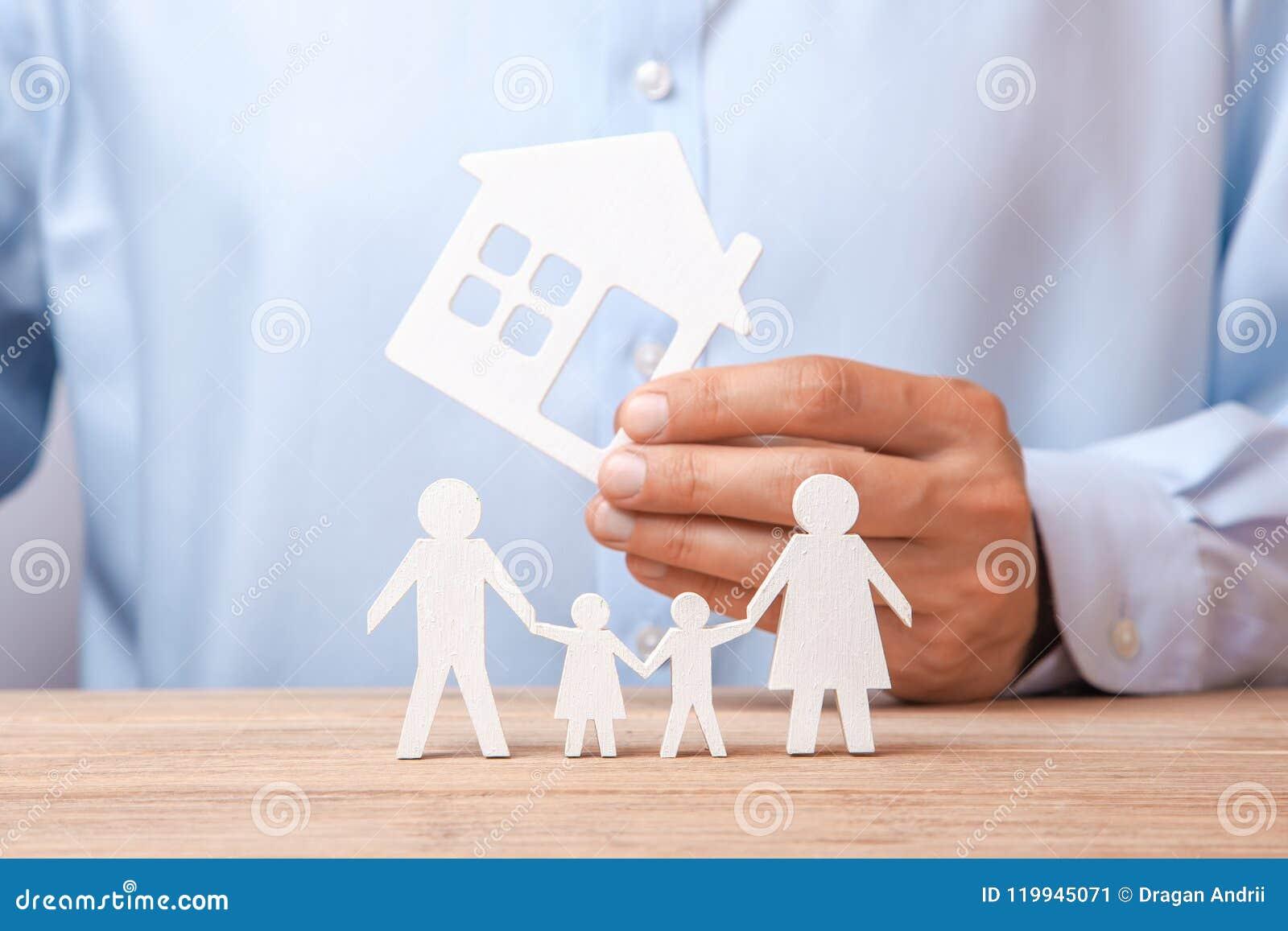Concept het huren van huis, krediet of verzekering De mens in overhemd houdt huis en de familie bevindt zich naast hem