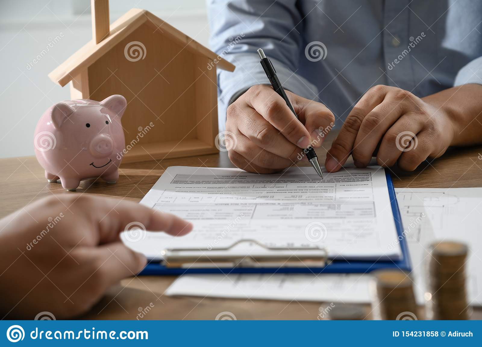 The concept of home ownership Business people negotiating a contract This is where you need to sign