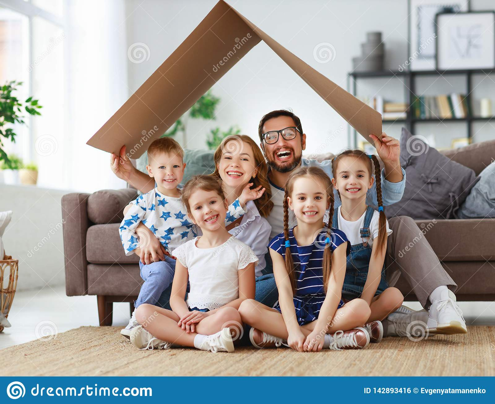 Concept of housing and relocation. happy big family mother father and kids with roof at home