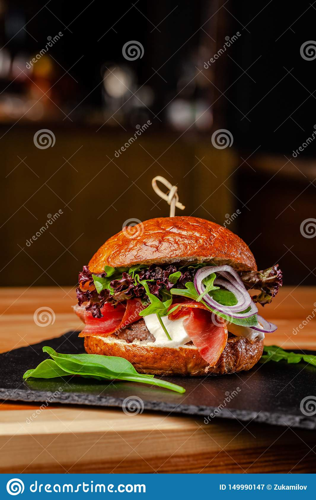 Concept of Italian home cooking. Burger with beef and pork meat cutlet, mozzarella cheese, salami sausage, parma, arugula